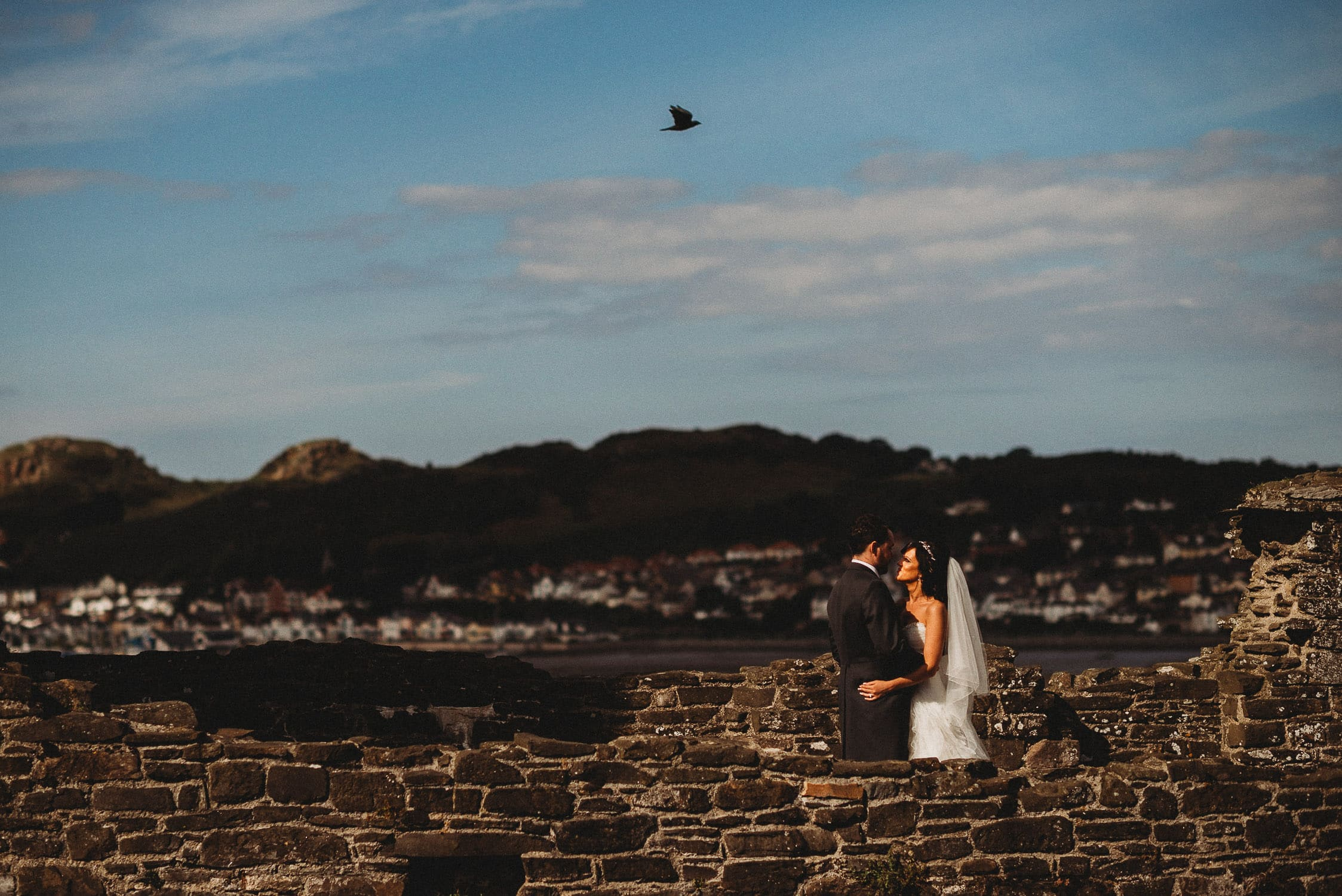 couple of newly married couple on their wedding day at Conwy Castle with a bird in the sky