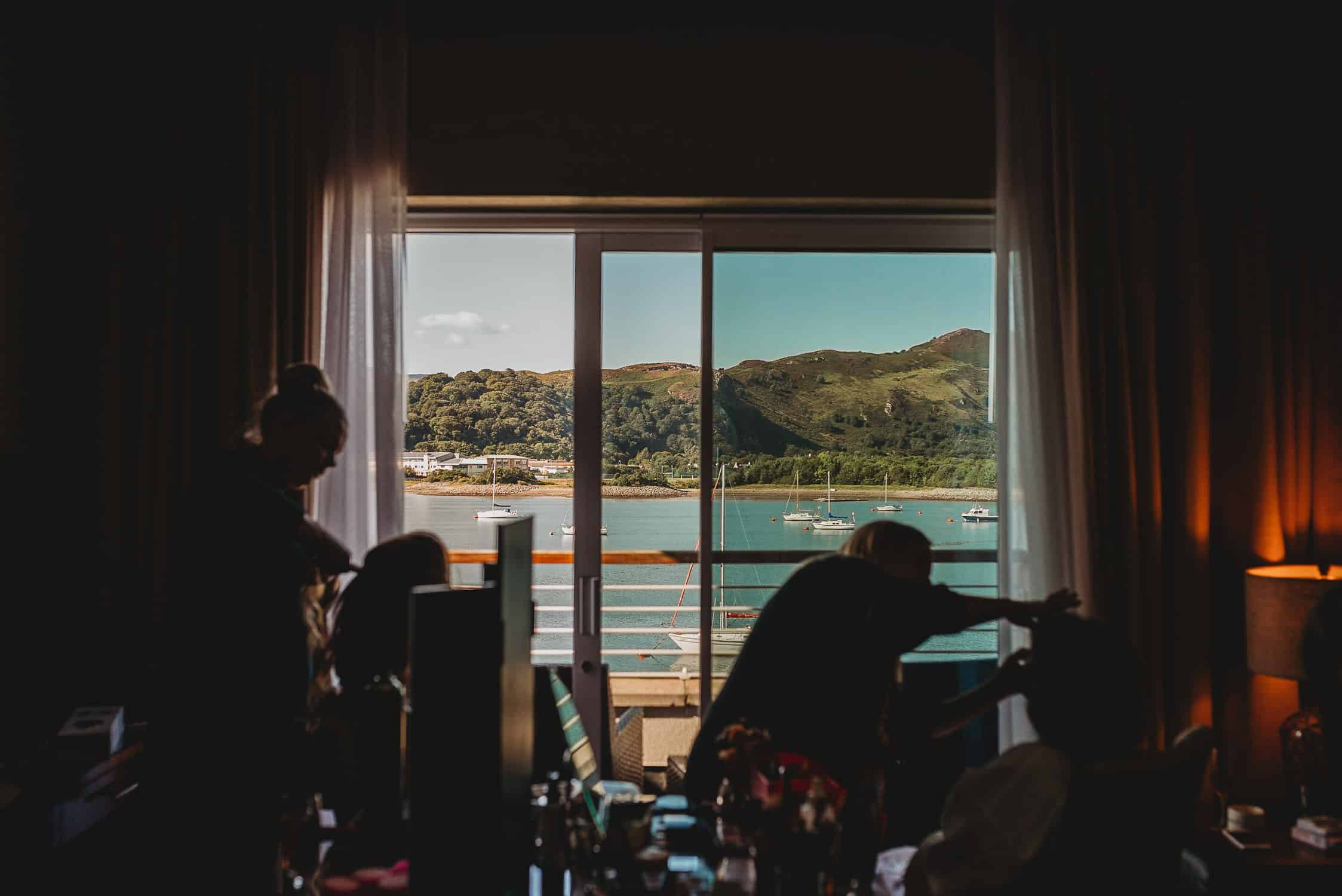 silhouette of bridal party having their make-up done against Conwy marina backdrop at The Quay Hotel Conwy North Wales