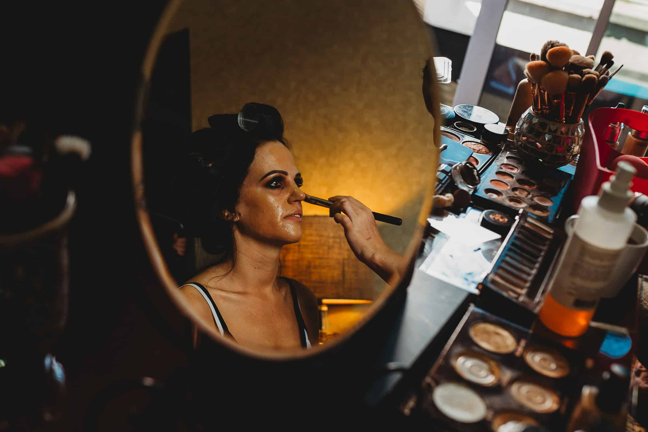 bride seen through mirror having make-up applied during bridal prep
