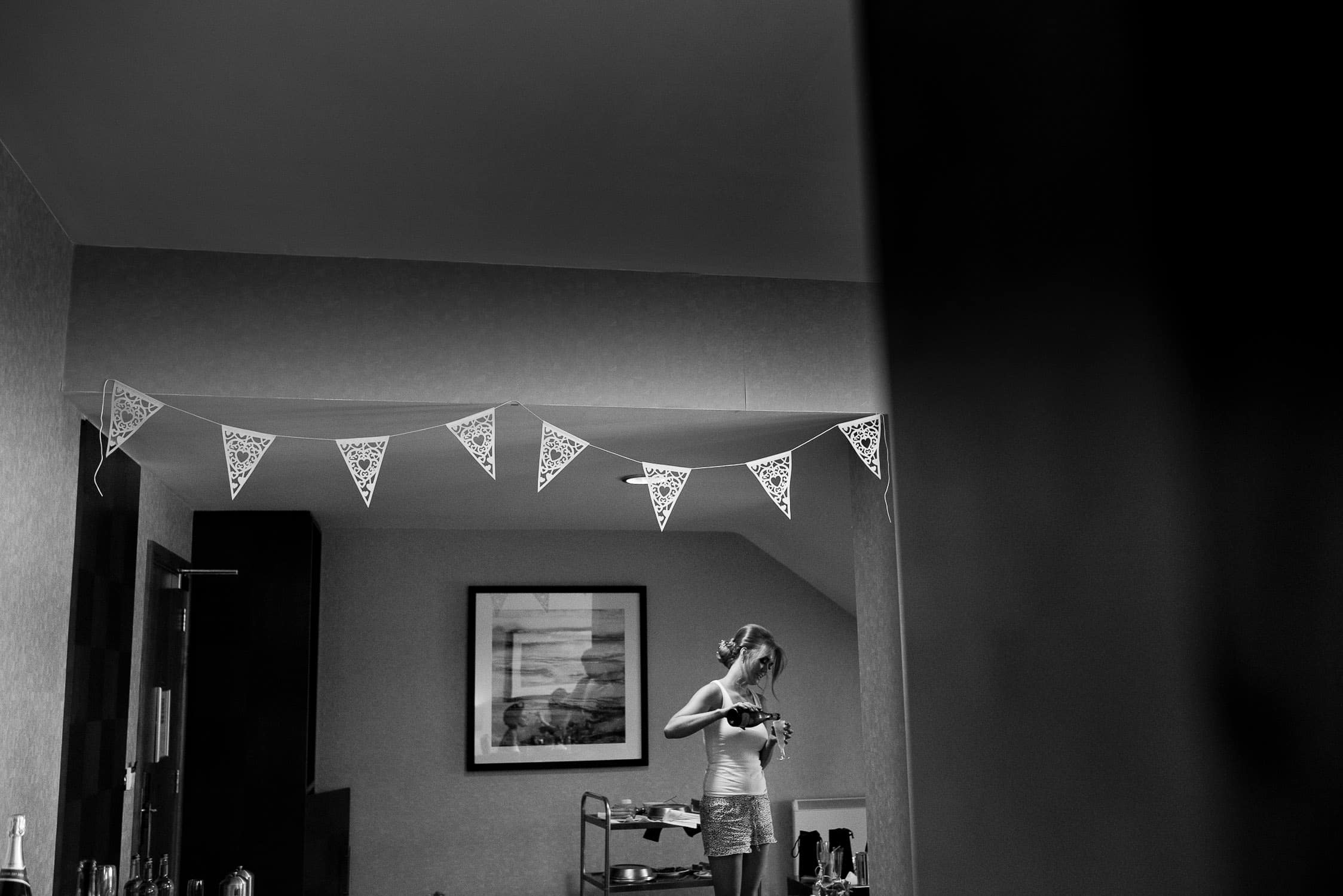 black and white image of bridesmaid pouring a glass of champagne with bunting across the room