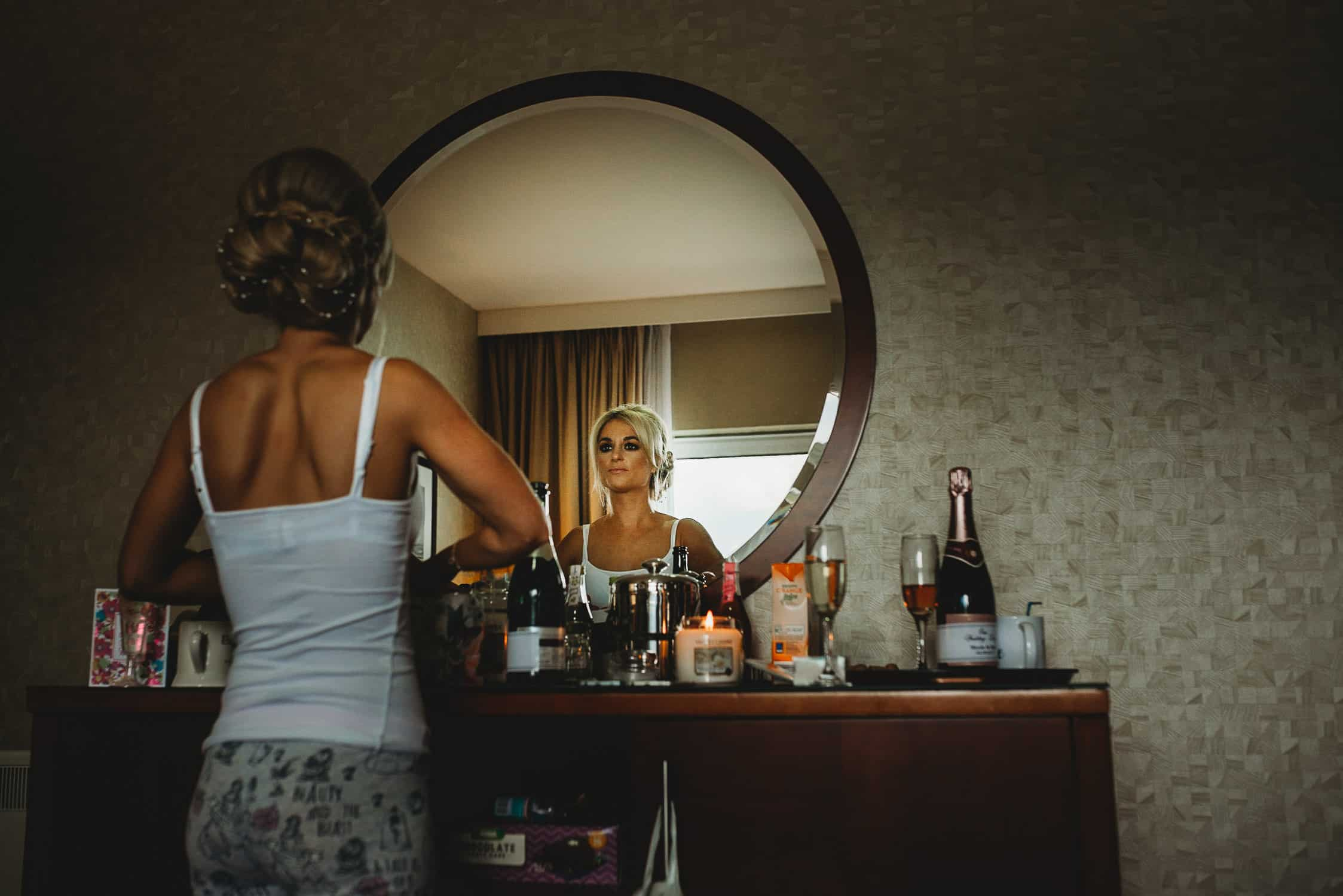 The Quay Hotel Wedding Photographer in Conwy North Wales bridesmaid looking at herself in the mirror during bridal prep
