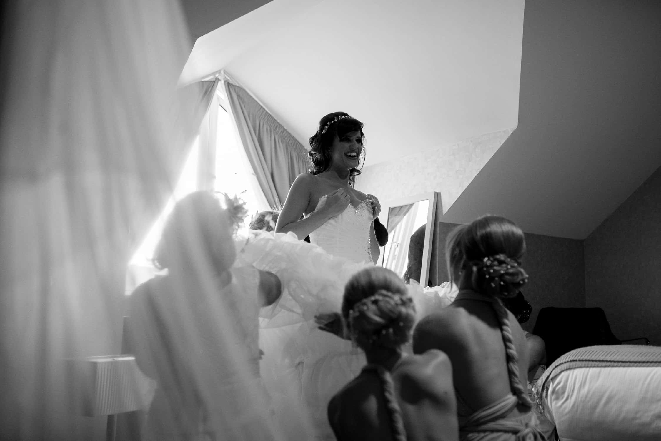 black and white image of bride holding her boobs while putting her wedding dress on assisted by her bridesmaids