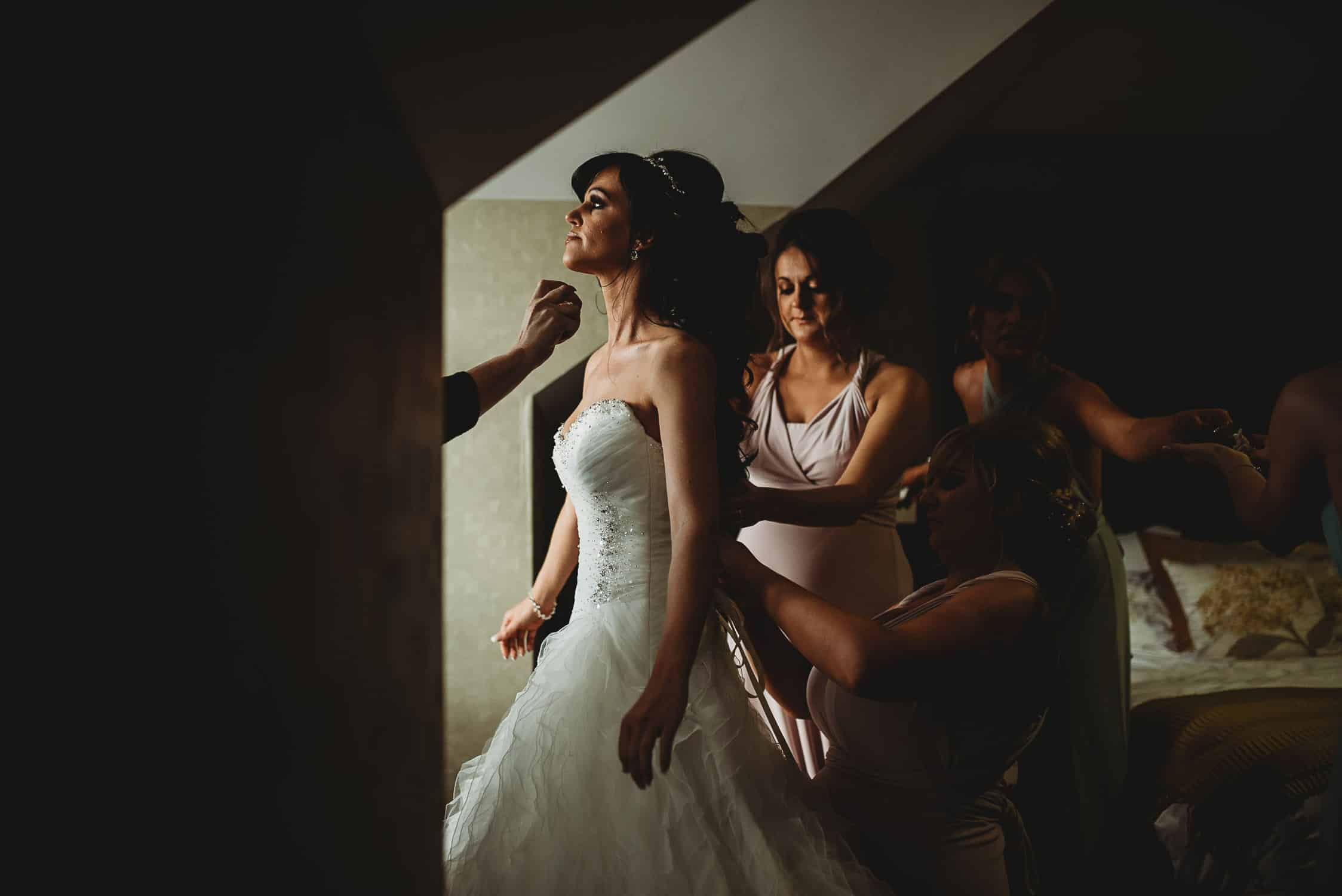 brides being helped into her dress by her bridesmaids while being sprayed with perfume at The Quay Hotel Wedding Photographer in Conwy North Wales