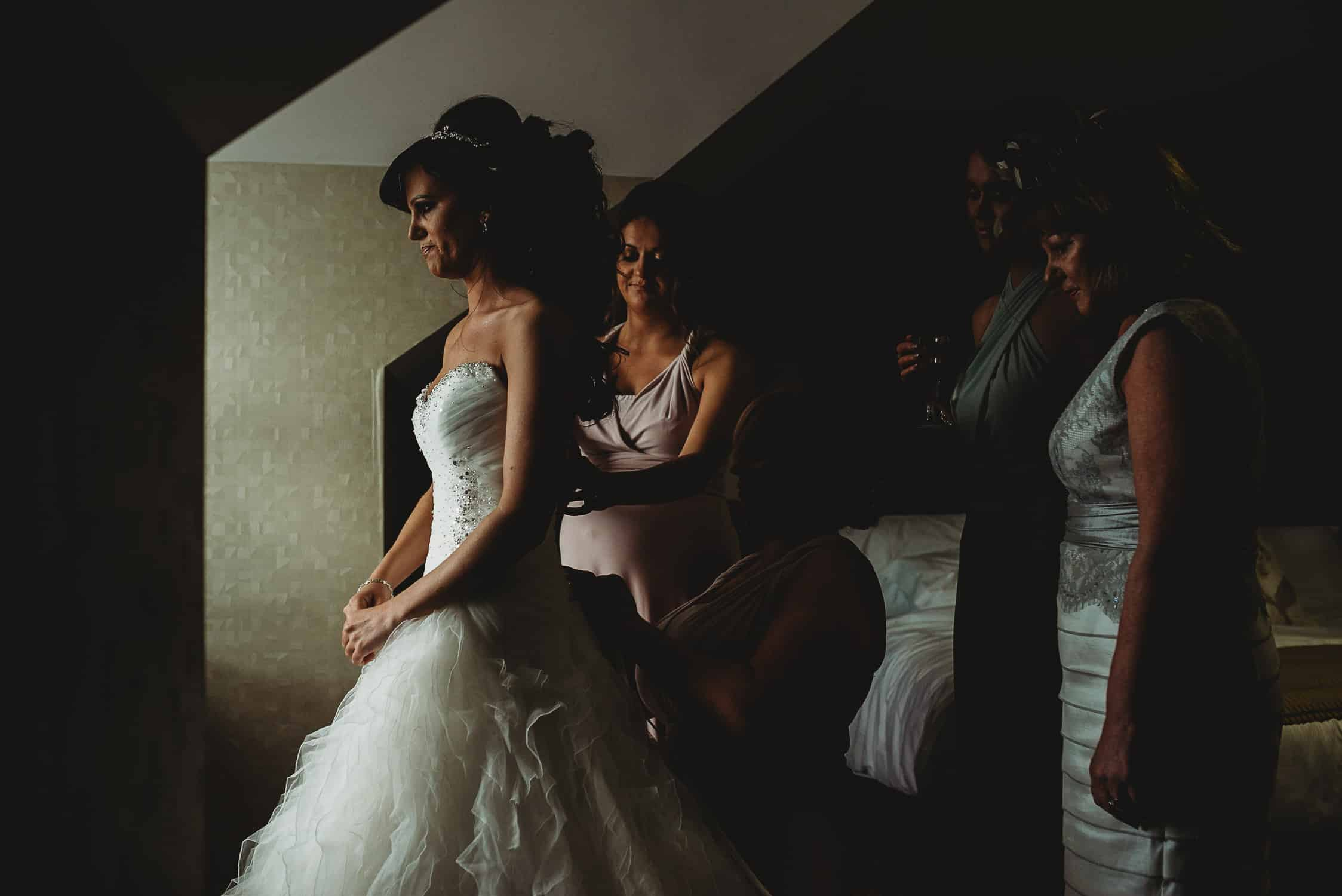 bride being helped into her dress by her bridesmaids with her mother looking on