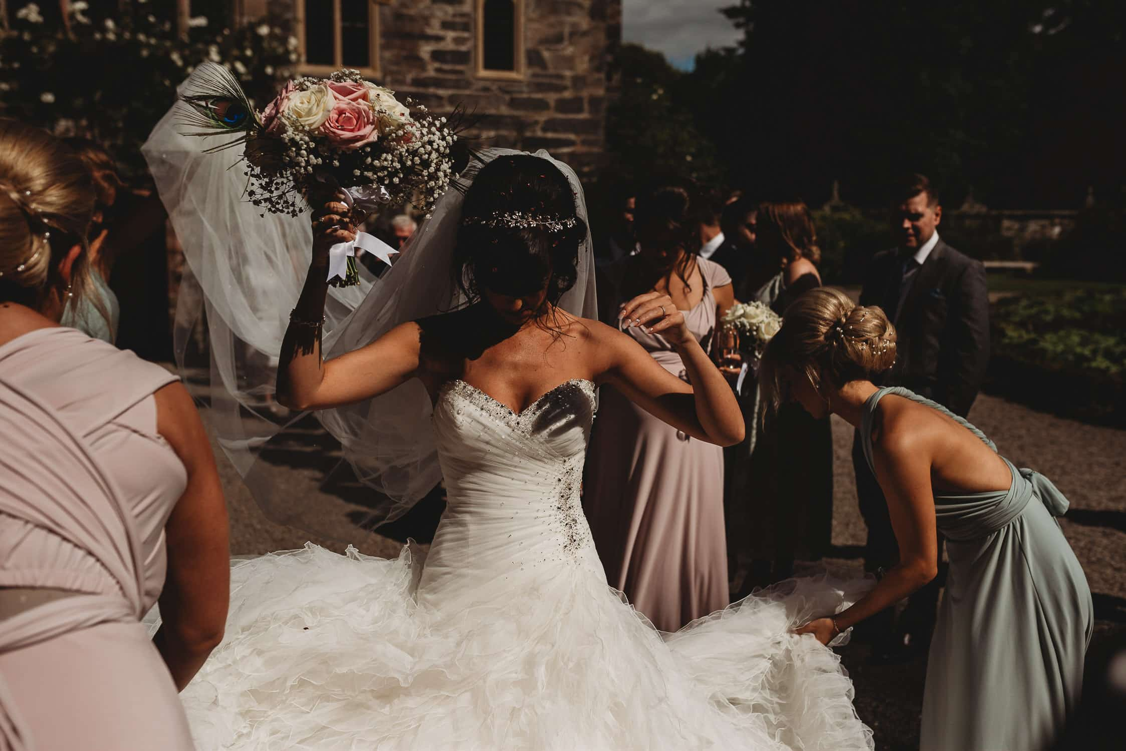 bridesmaids getting confetti off the bride's dress with bride raising bouquet above her head