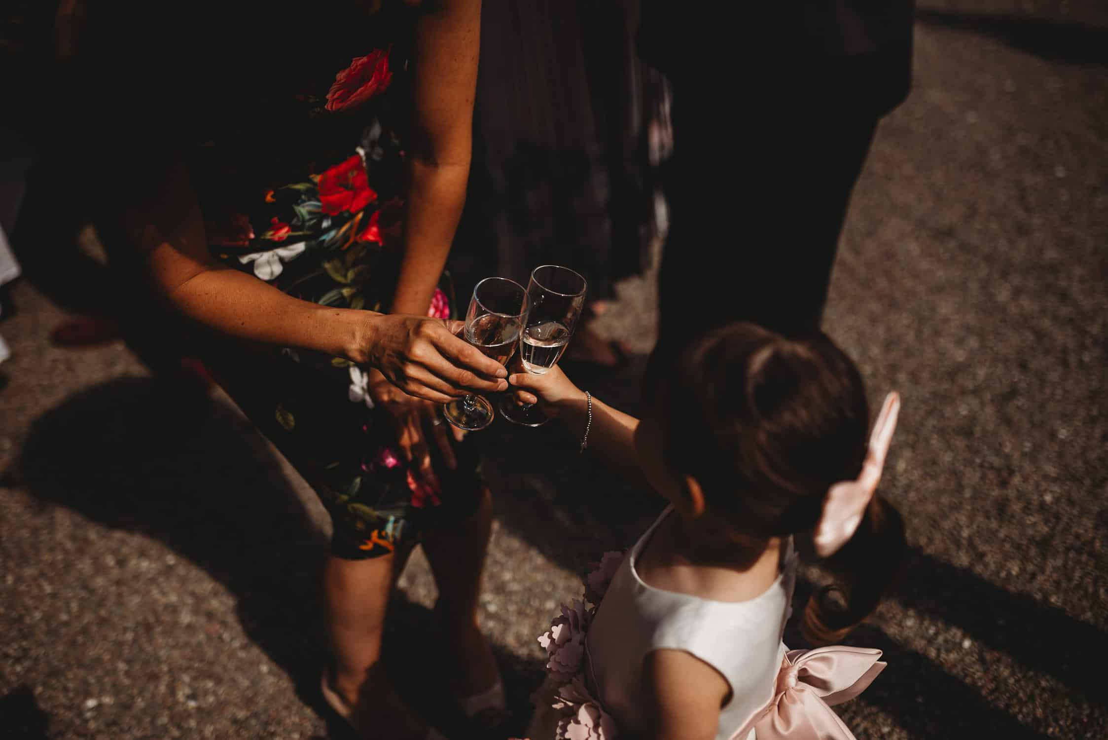 close-up of little girl toasting wedding guest with a glass of champagne