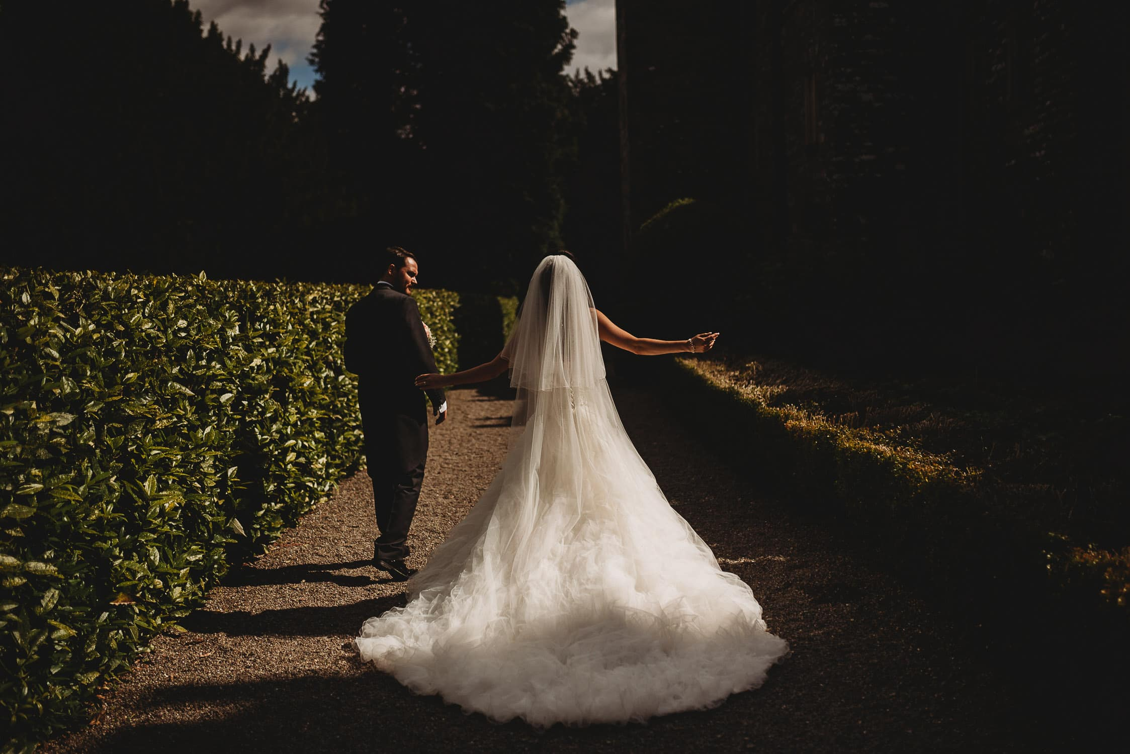 bride walking with her arms stretched out in big fluffy wedding dress at Gwydir Castle