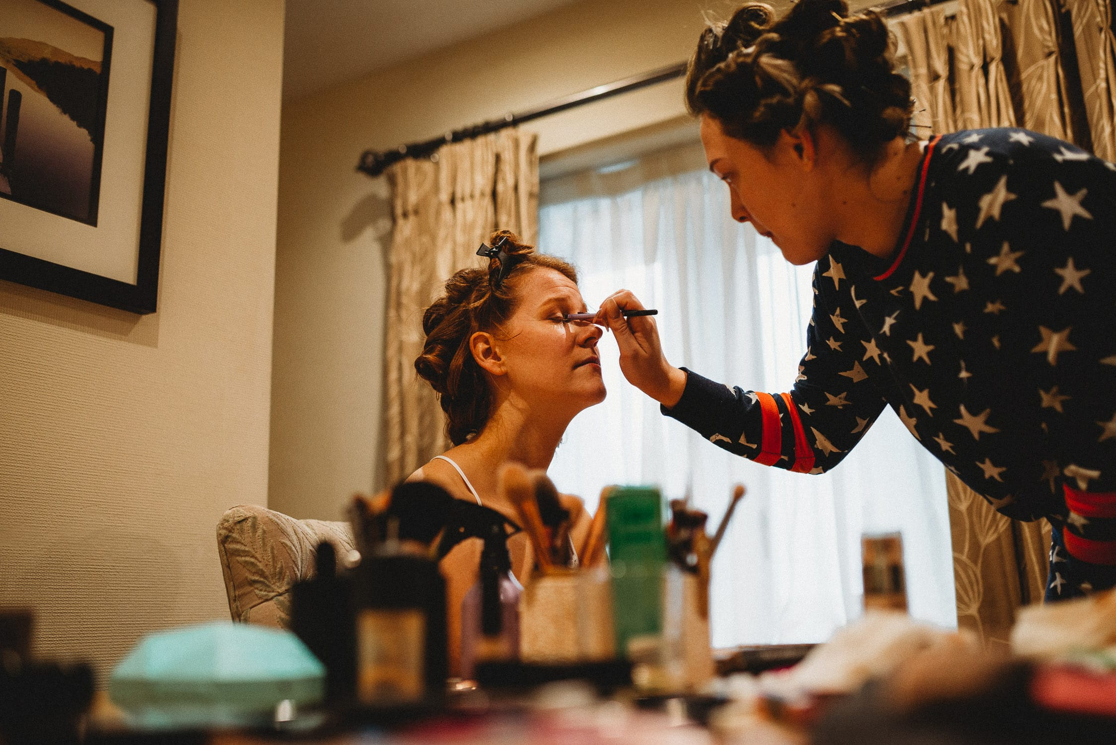 bride having her make-up done during bridal prep at Stirk House