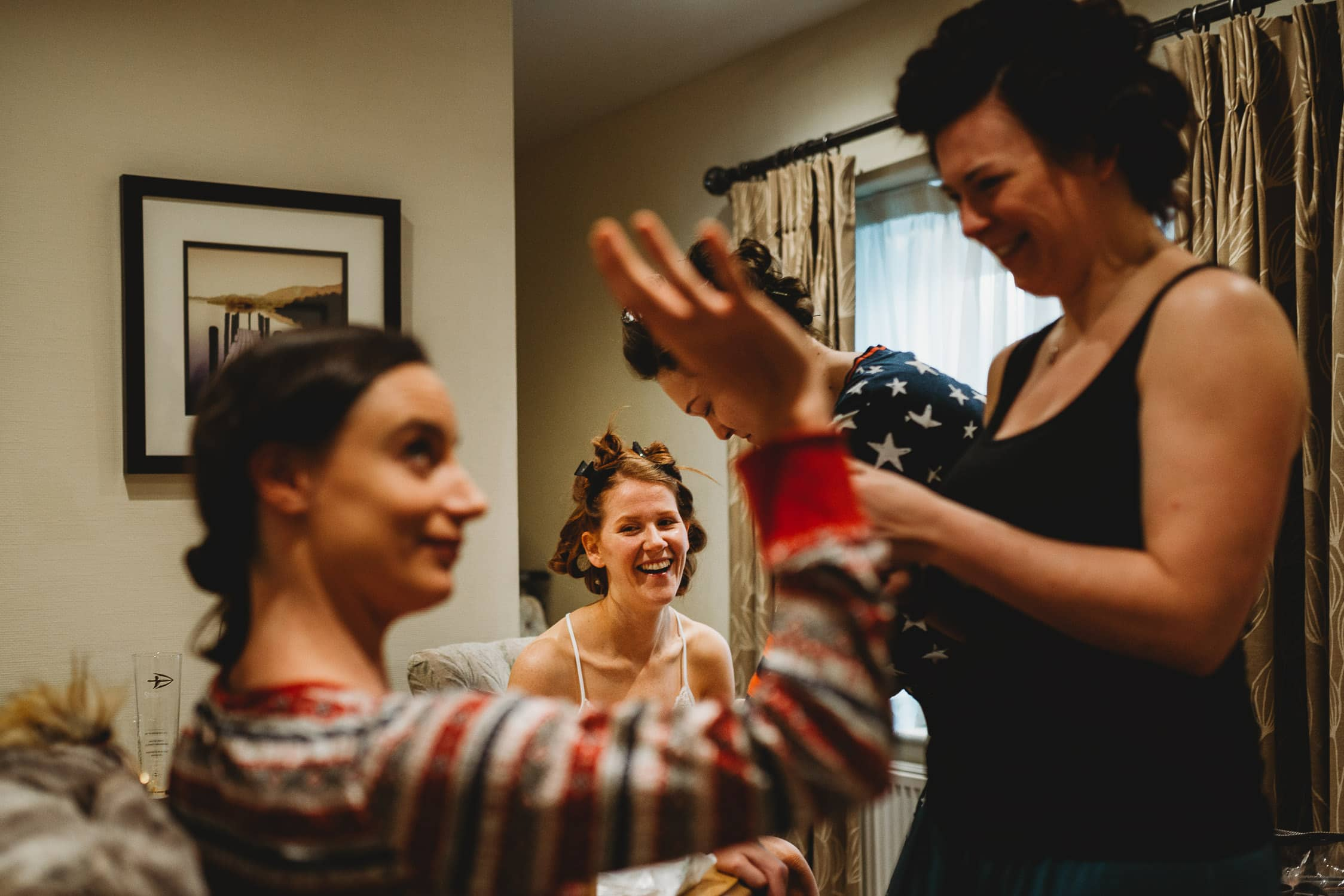 bride smiling at her bridesmaids during bridal prep