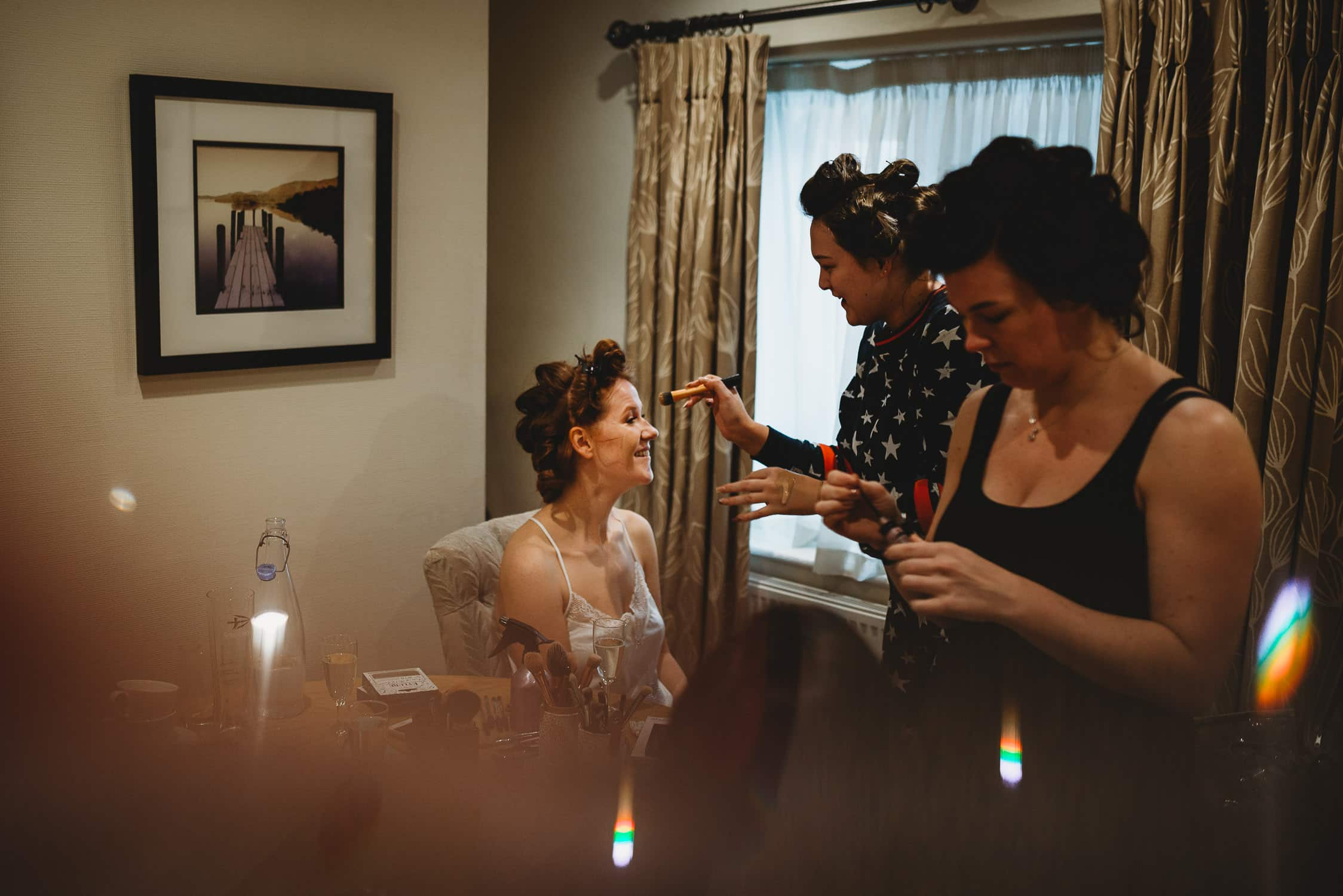 bride laughing with two of her bridesmaids during bridal prep