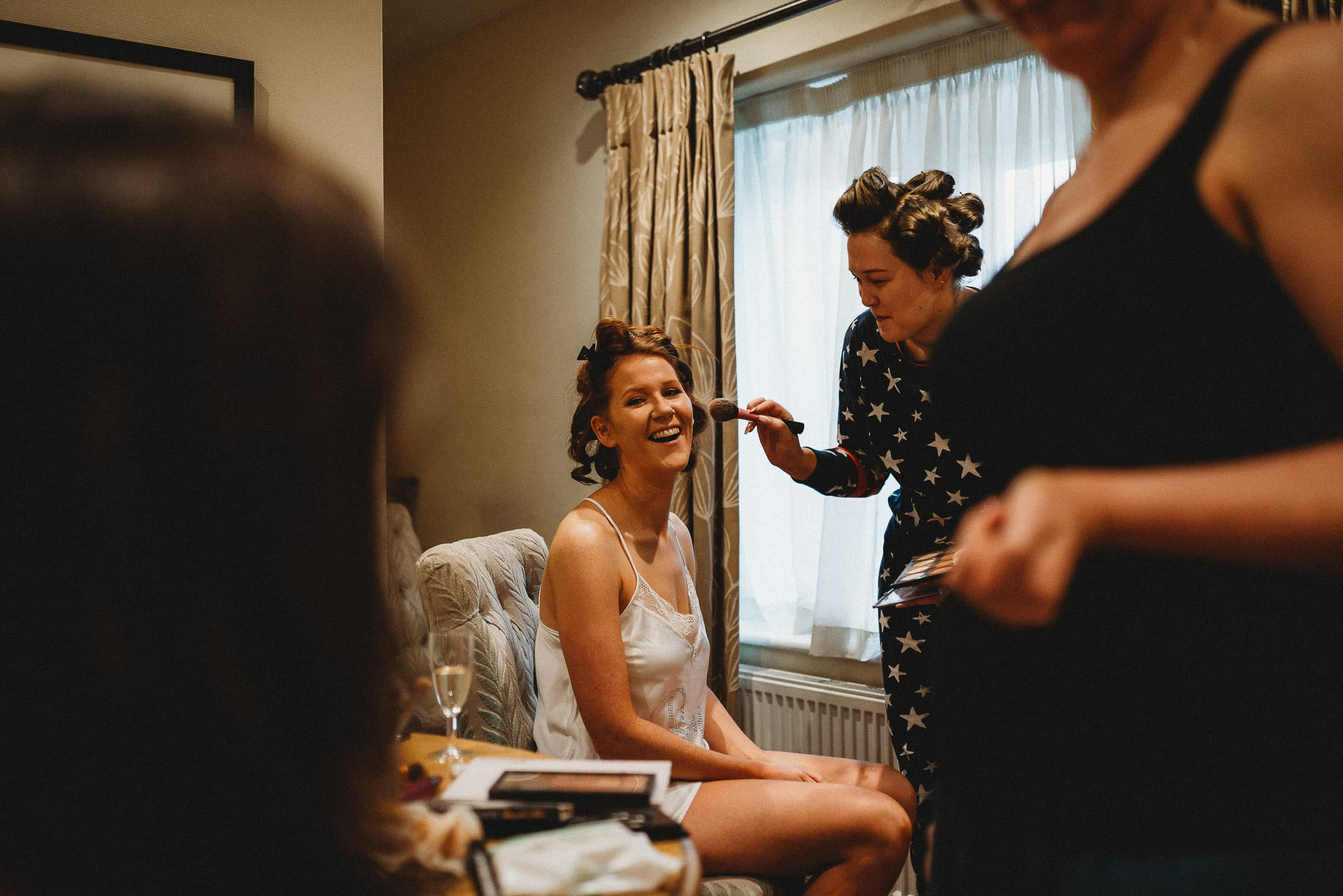 bride laughing at bridesmaids during bridal prep at Stirk House