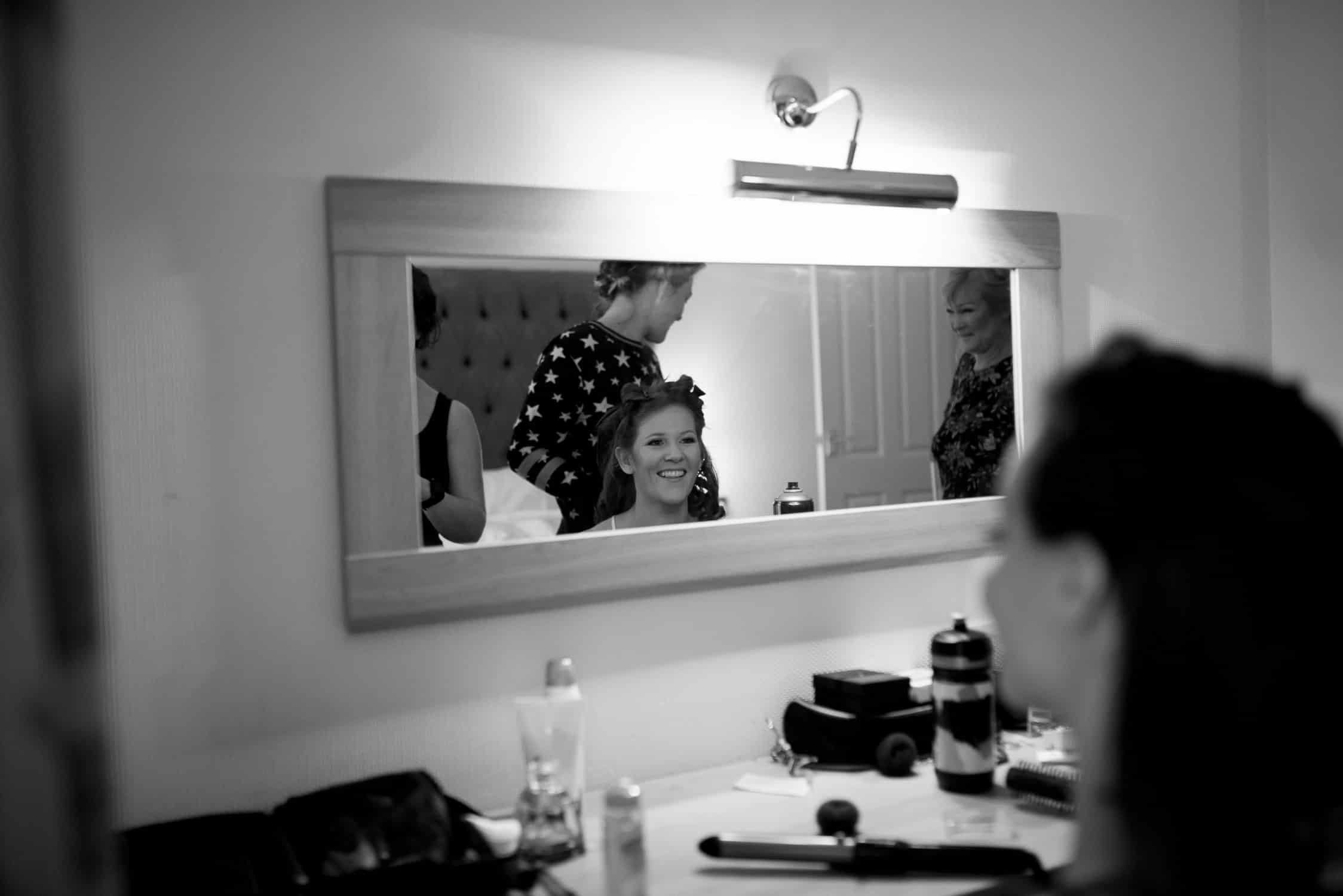 black and white image of bride smiling at her mum and bridesmaids in mirror's reflection