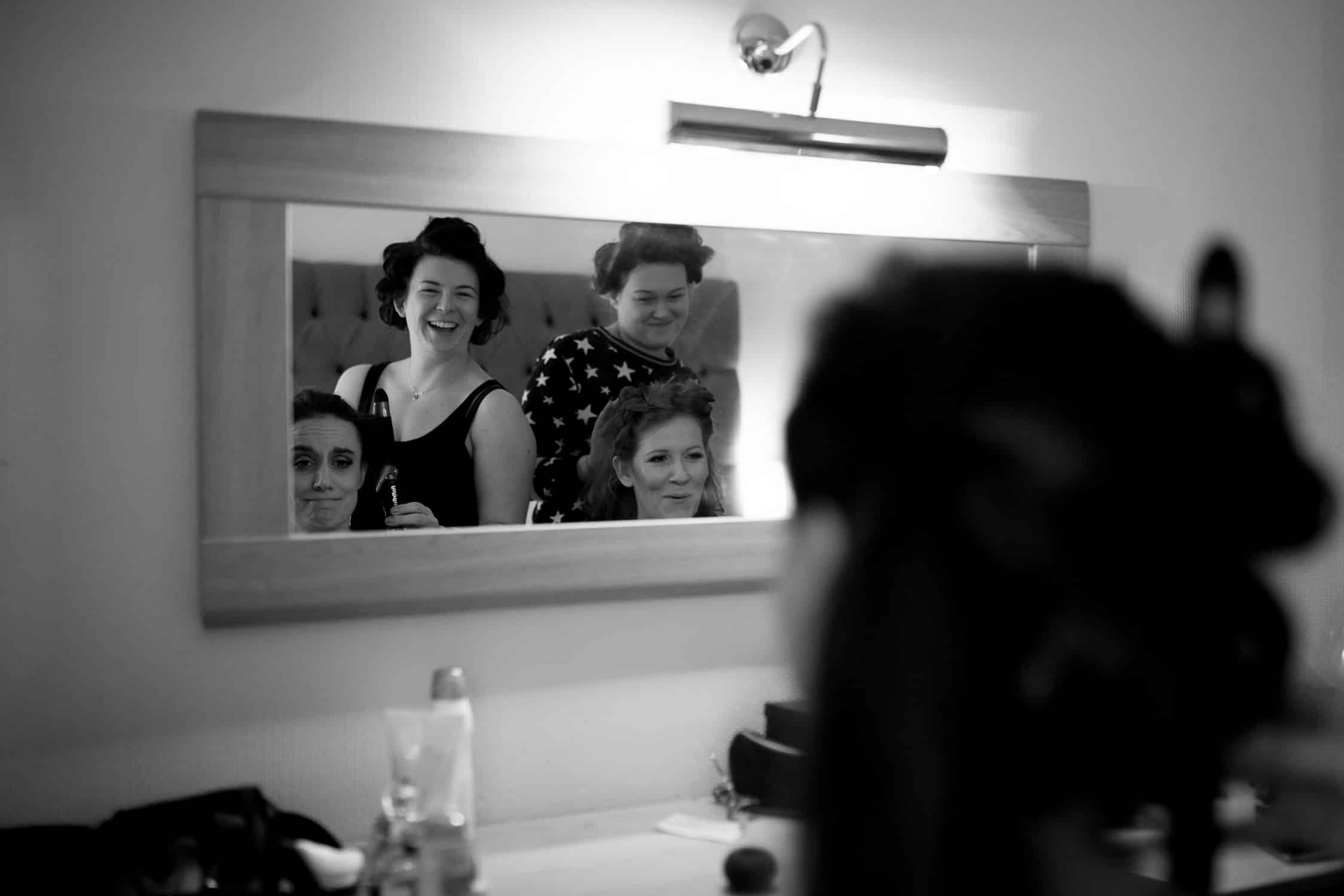 black and white image of bride and one of her bridesmaids pulling faces while another two bridesmaid smile at them in mirror's reflection