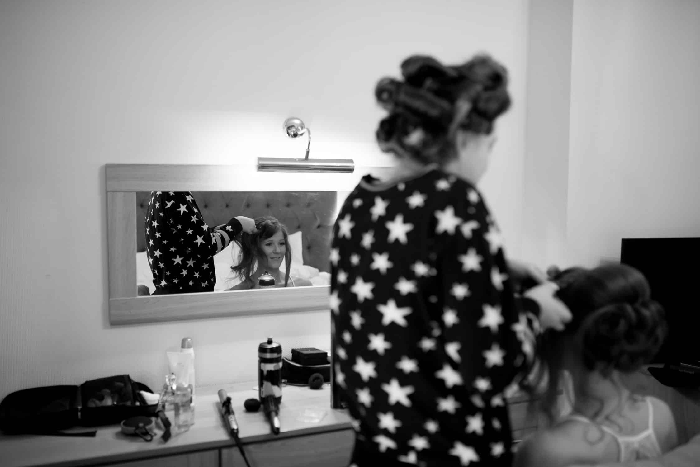 black and white image of bride's reflection in the mirror while having her hair done