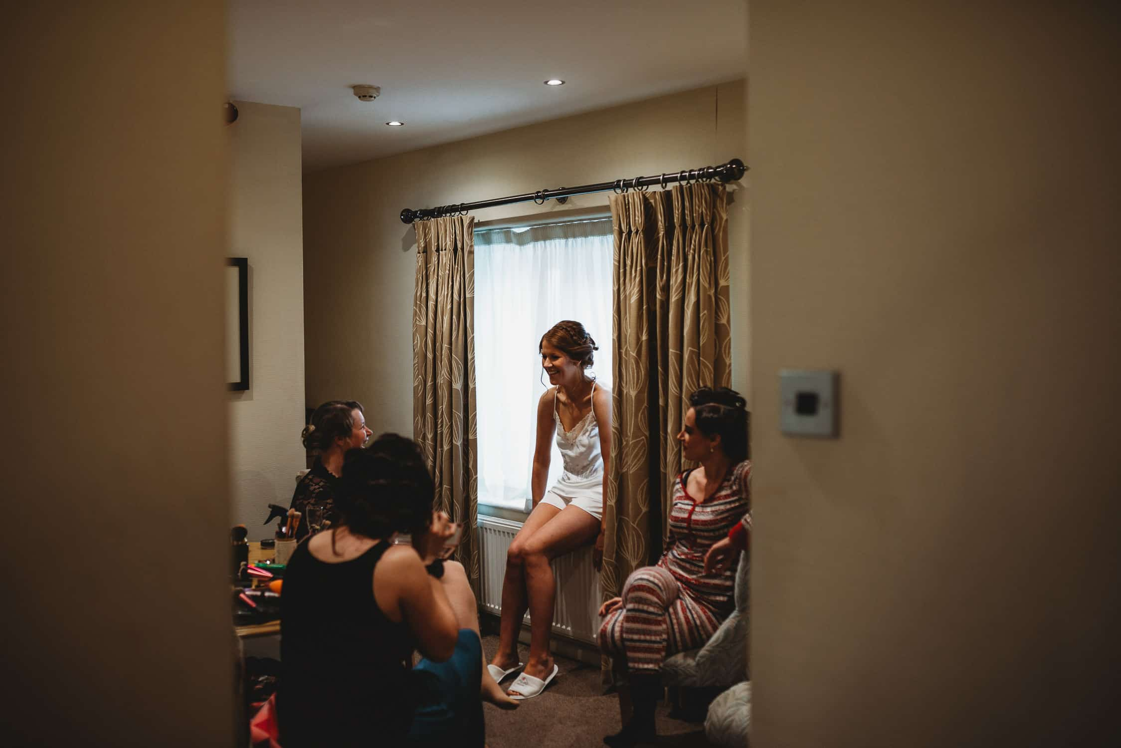 group picture of bride and bridesmaids during bridal prep at Stirk House in Lancashire framed through doorway