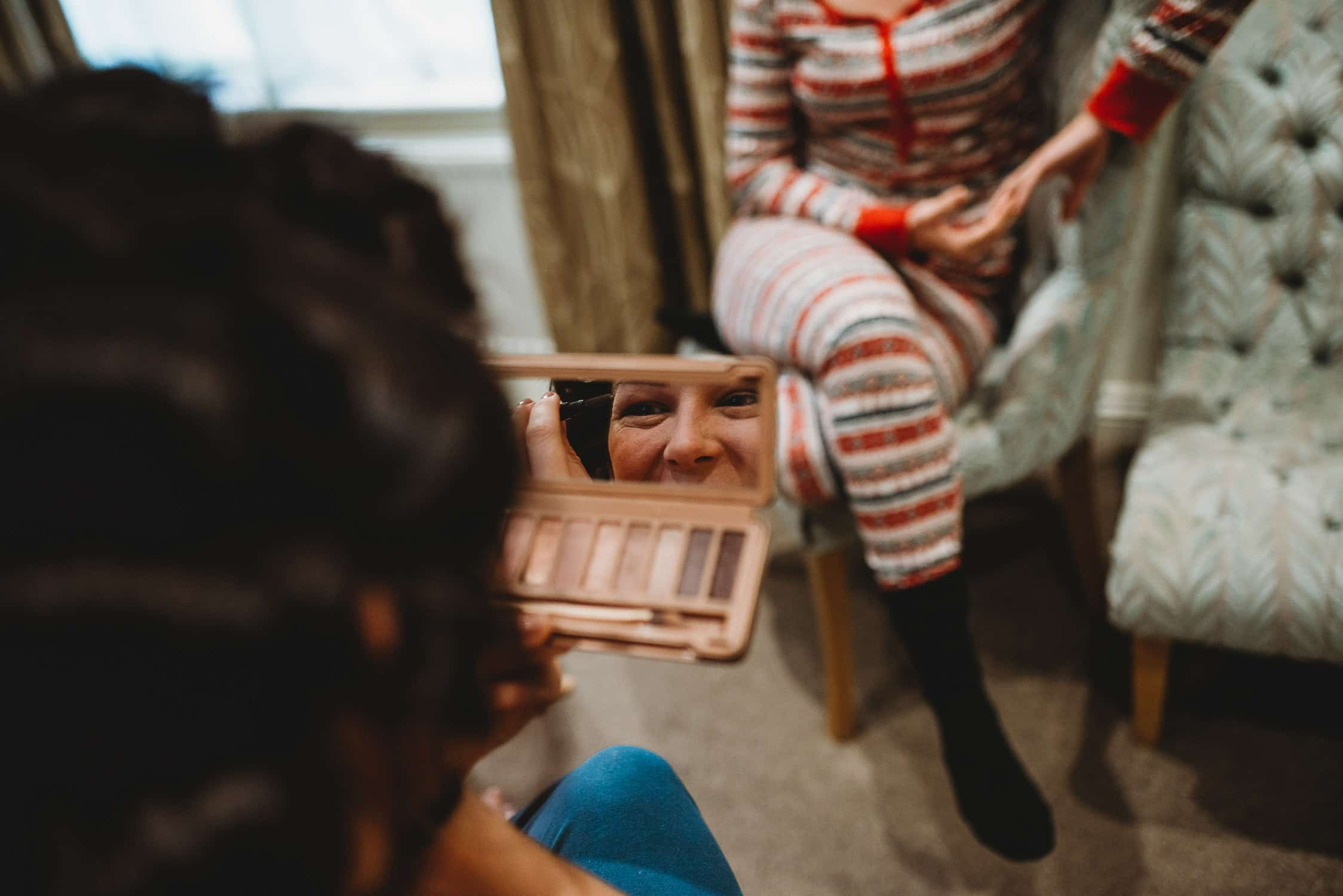 bridesmaid checking her make-up in hand held mirror