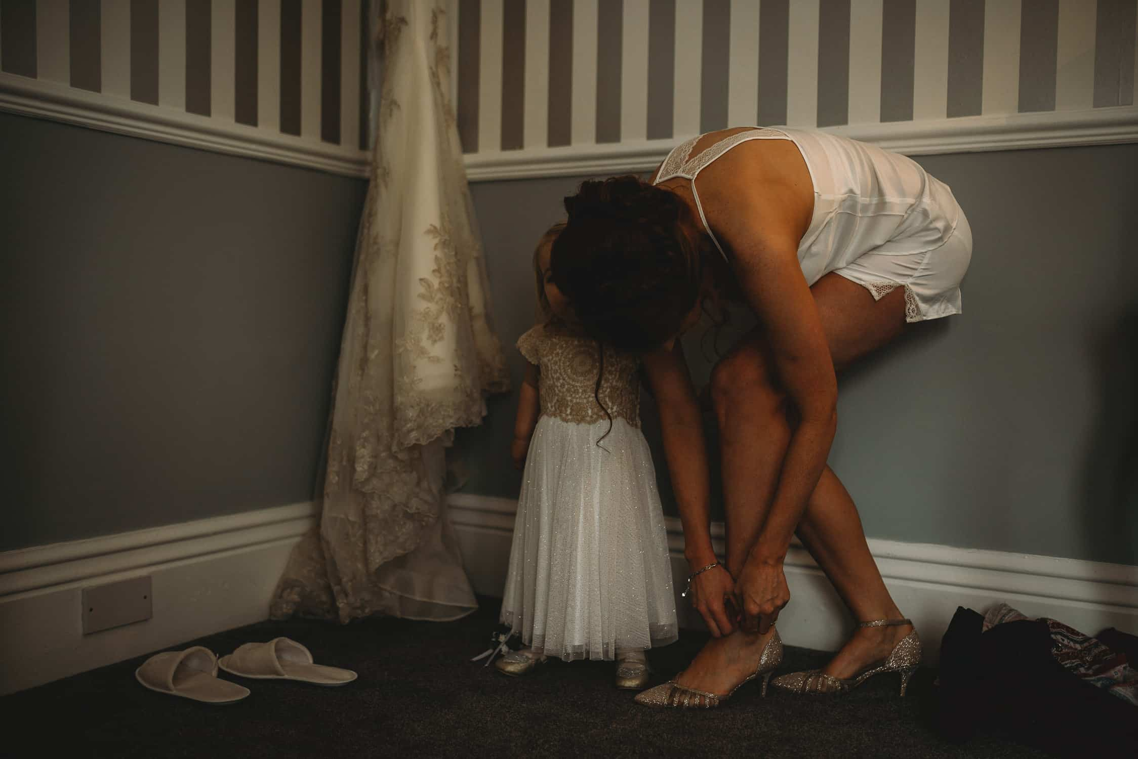 bride putting her shoes on with her little girl beside her