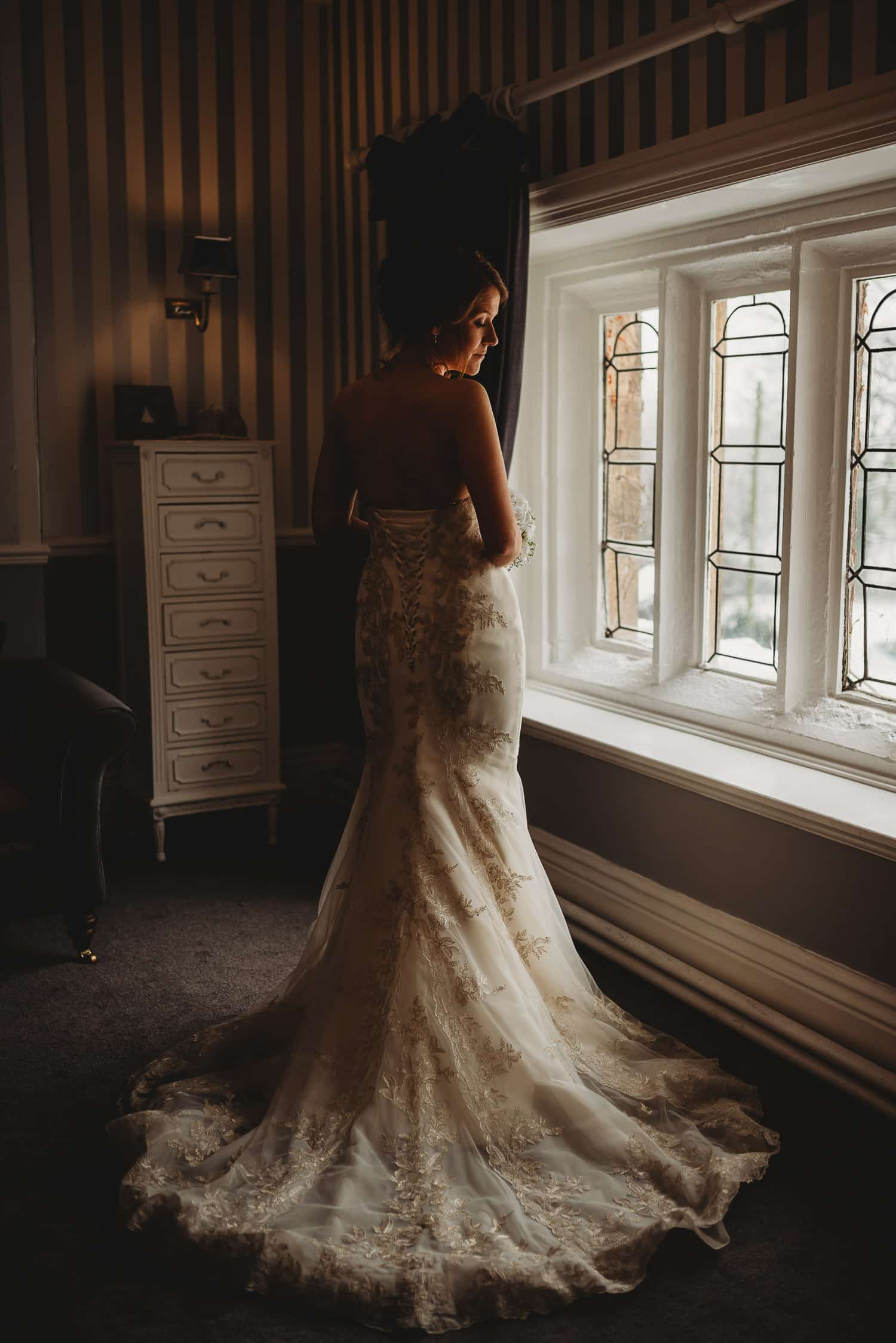 portrait of bride in her dress opposite window