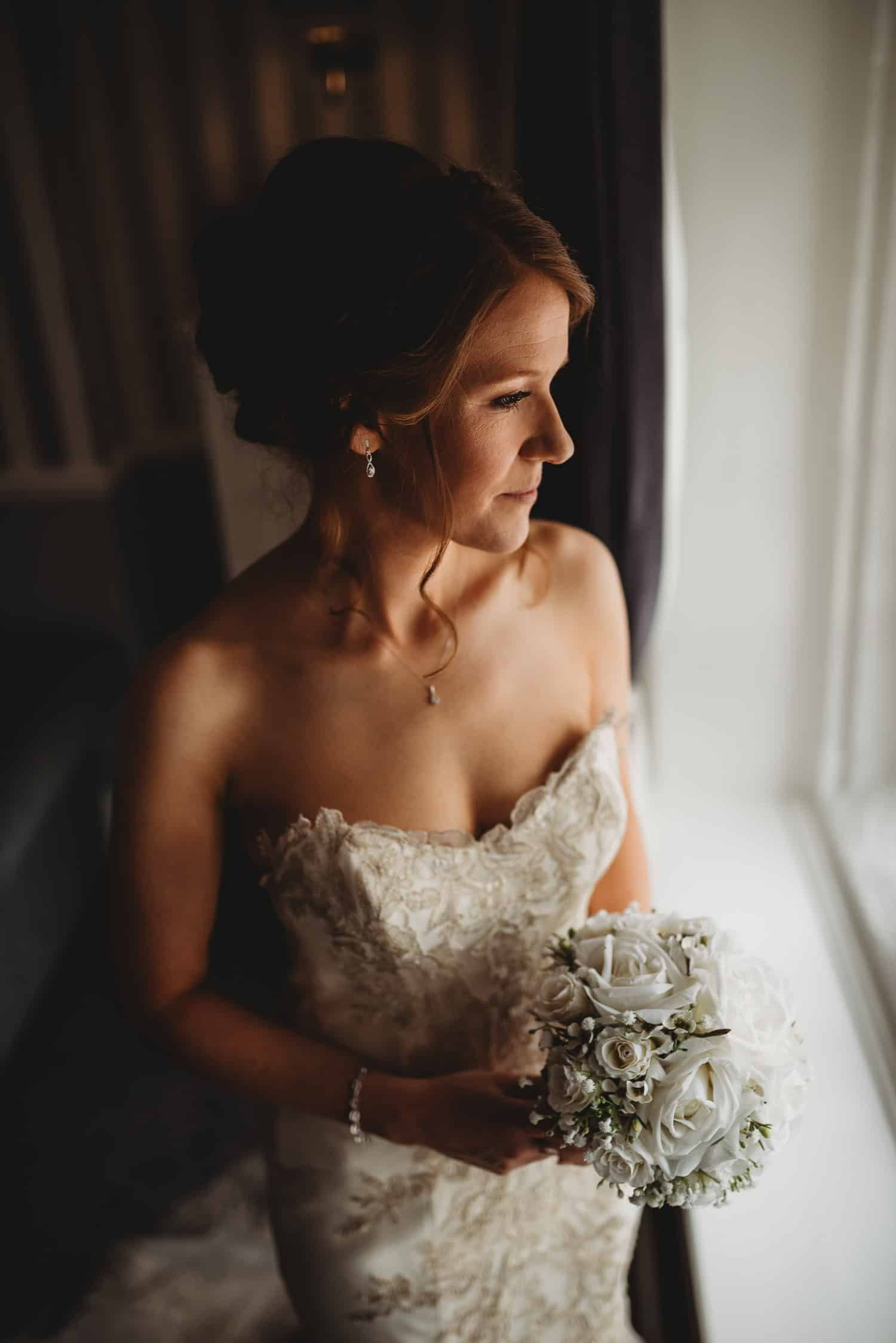 portrait of the bride holding her bouquet and looking out of the window