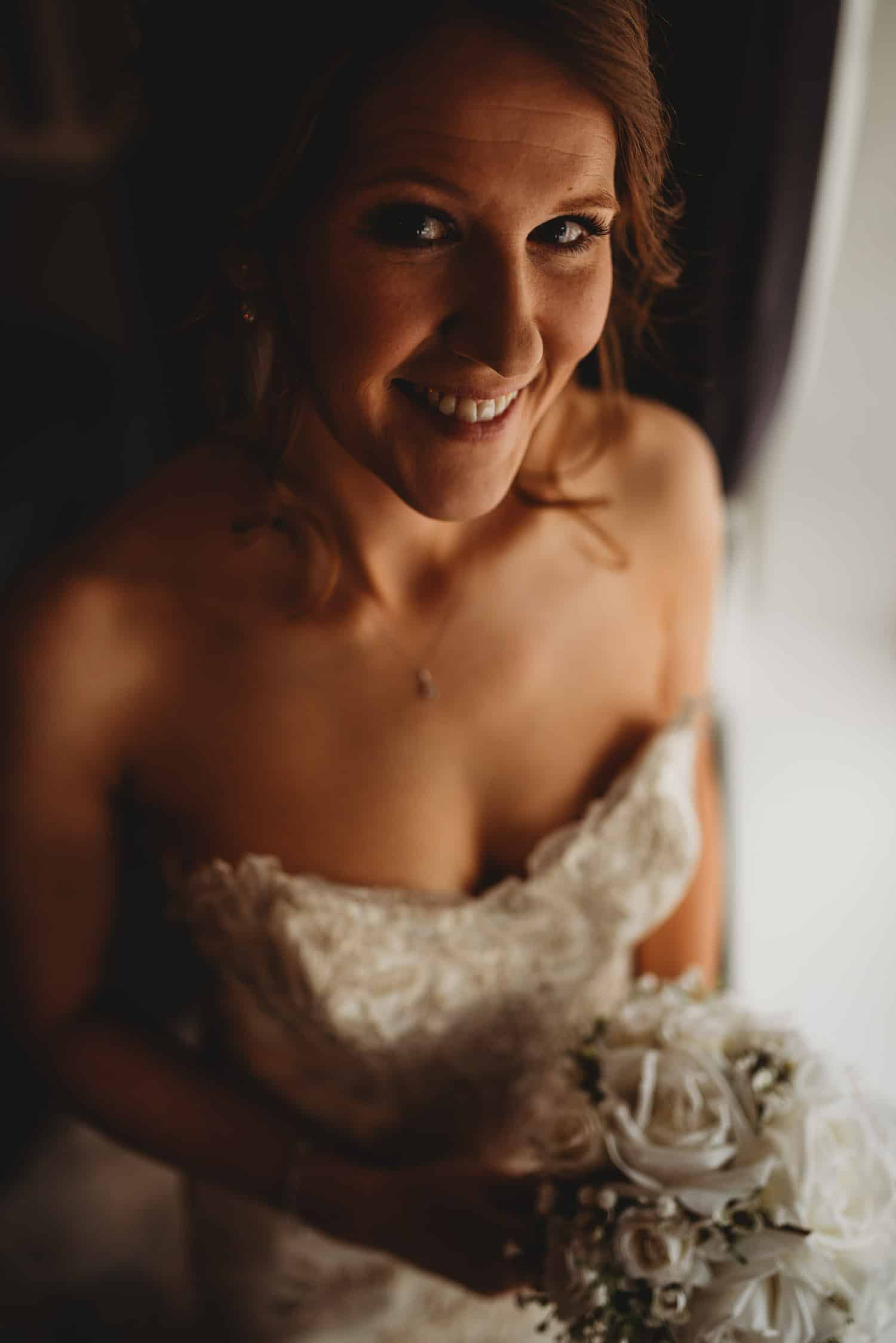 portrait of bride smiling at the camera while holding her bouquet