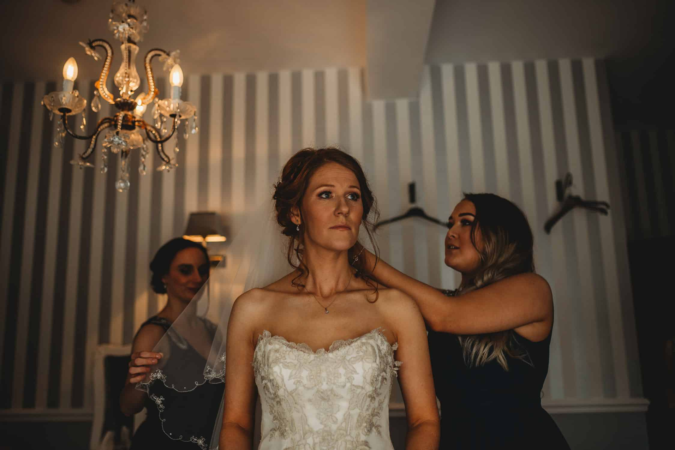 bride's veil being adjusted by her bridesmaids