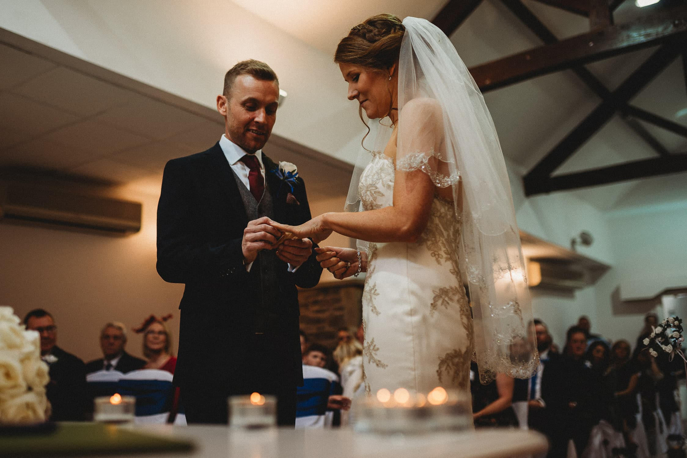 groom putting ring on bride's finger during ceremony at Stirk House in Lancashire