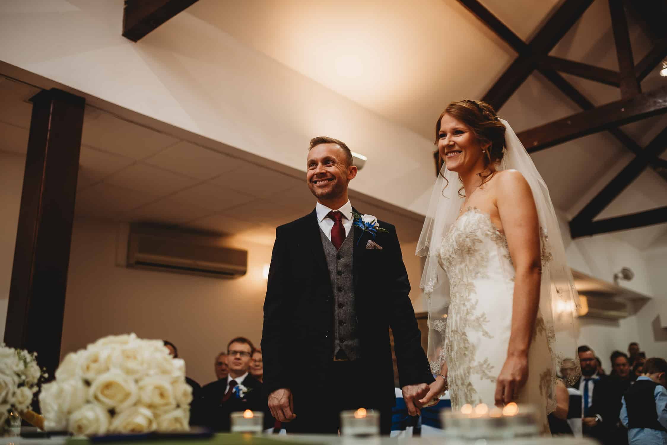 bride and groom smiling at the registrar during their wedding ceremony at Stirk House in Lancashire