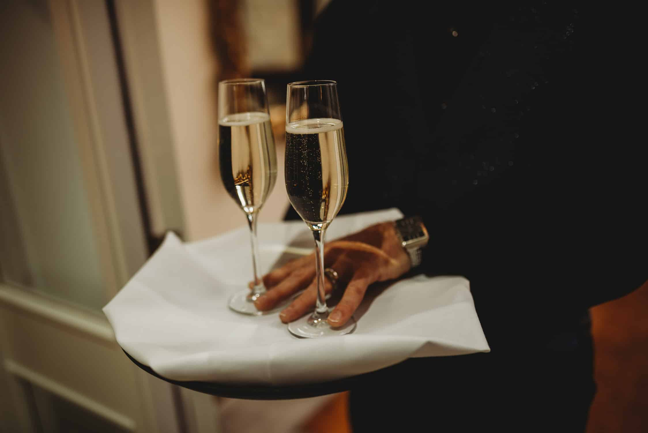 close-up of two glasses of champagne on a tray covered by a white napkin
