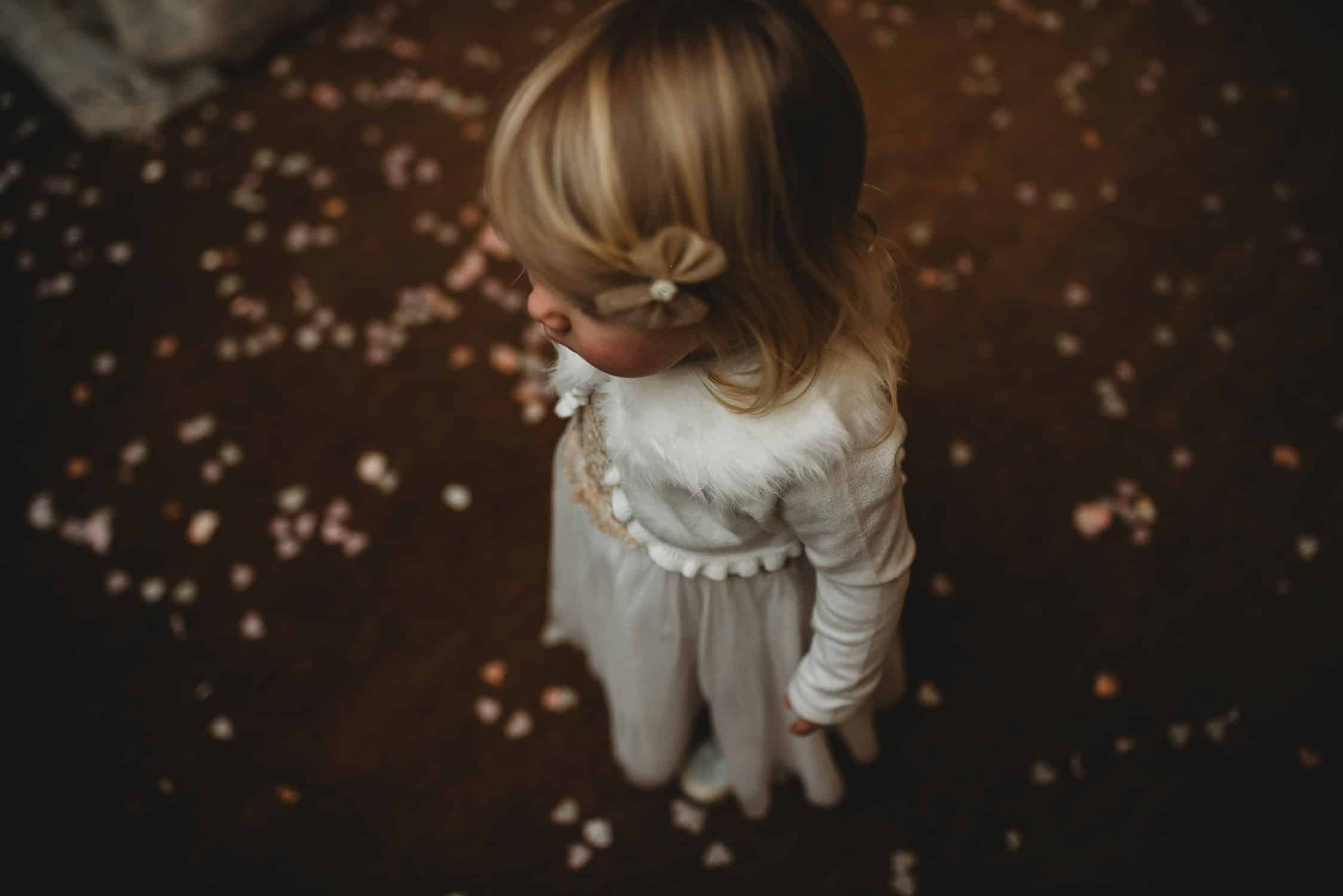 close-up of little girl from above with confetti on the floor