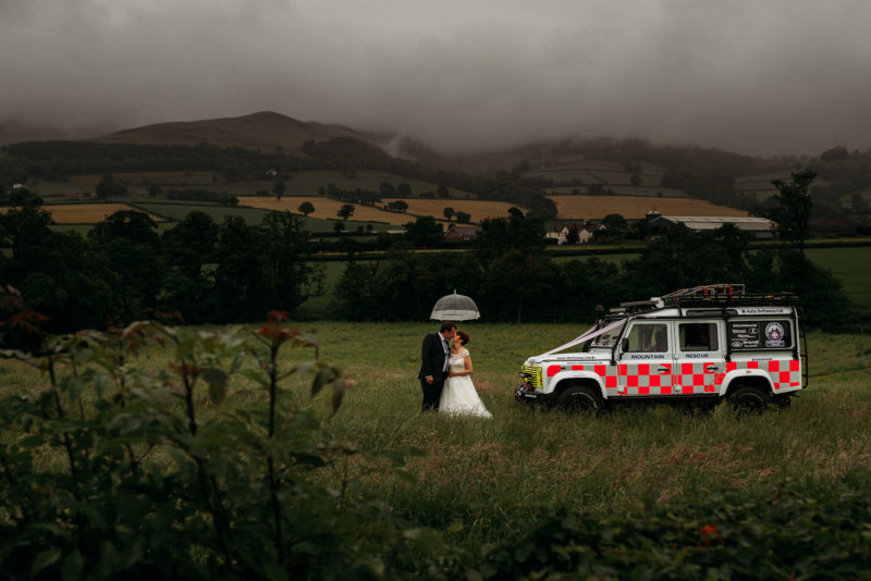 Vale Country Club Wedding PhotographerBridal portrait of Search & Rescue bride & groom with Landrover in a field