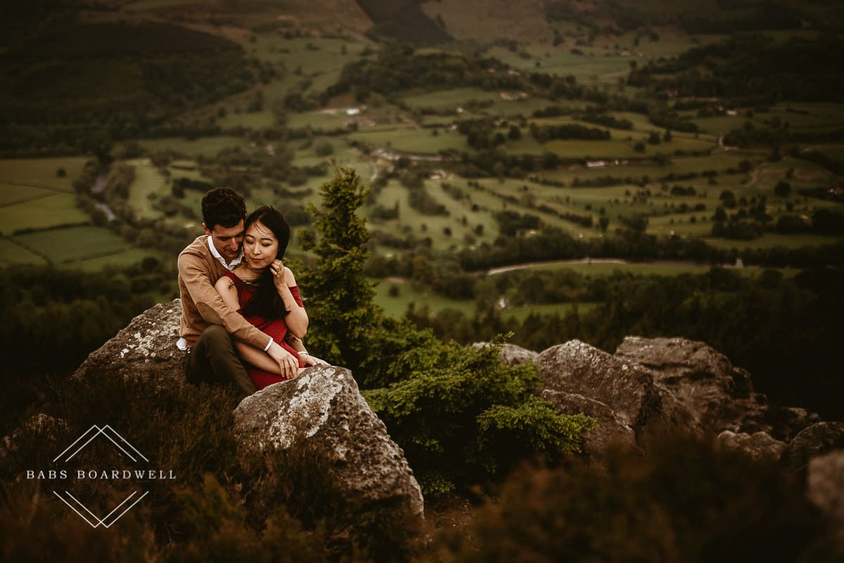 couple sitting on a rock against a valley backdrop