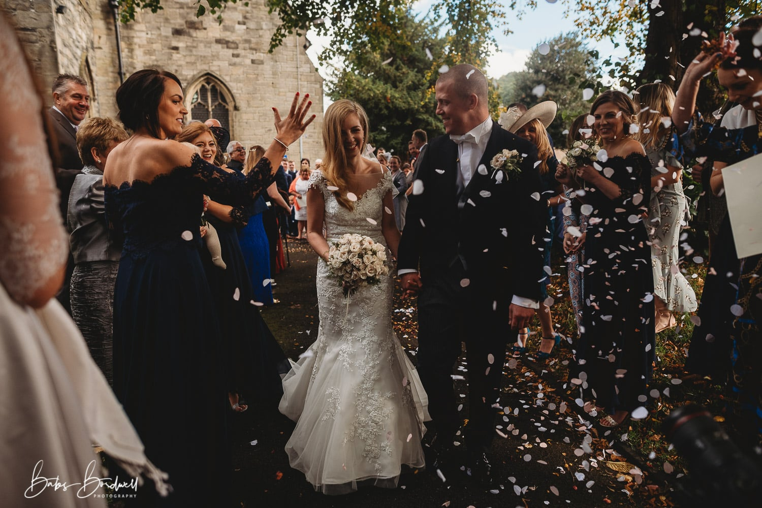 bride and groom walking through guests throwing confetti at them