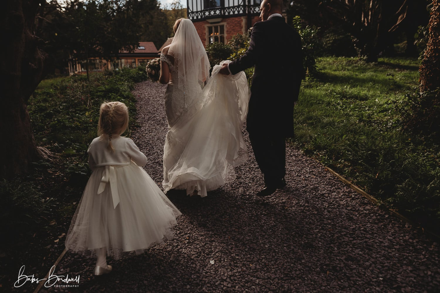 bride and groom walking with groom holding the bride's dress up and a flower girl following them at Tyn Dwr Hall