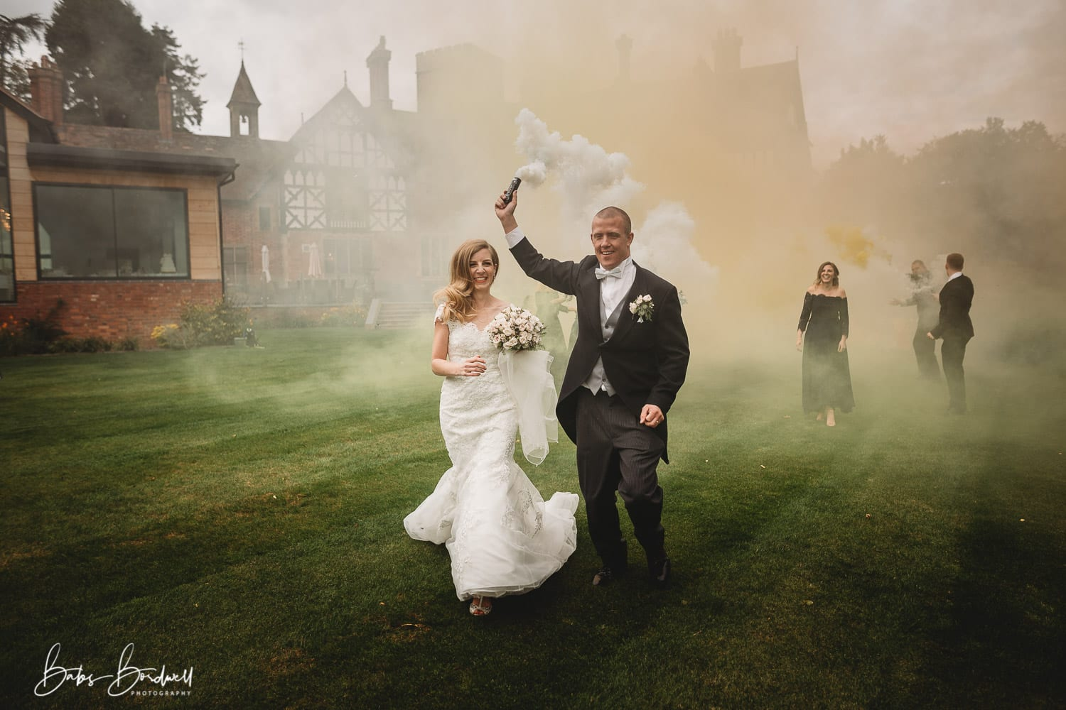 couple running with groom holding white smoke bomb at Tyn Dwr Hall