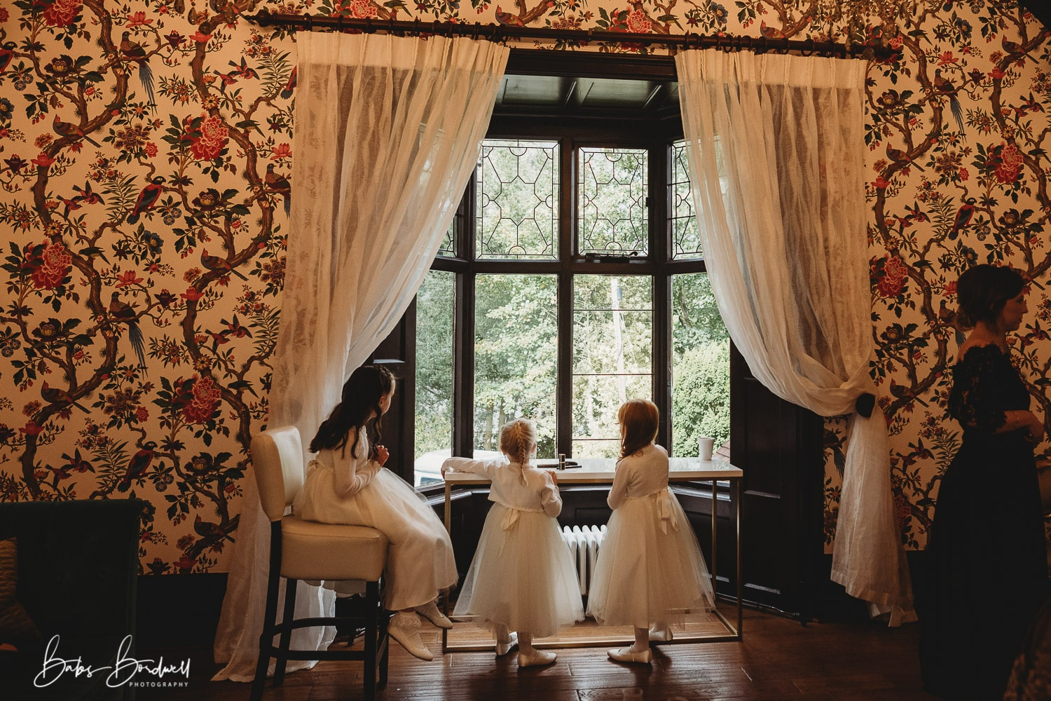 3 little flower girls looking out of the window at Tyn Dwr Hall