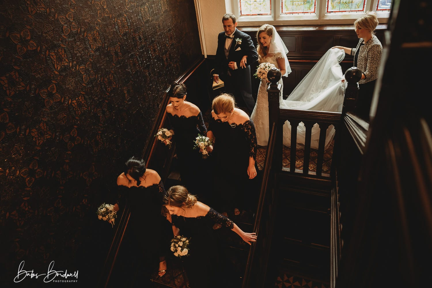 bride walking down the stairs at Tyn Dwr Hall behind her bridesmaids and on her father's arm