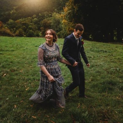 couple walking hand in hand at Llantysilio with bride wearing blue wedding dress by Best North Wales Wedding Photographer