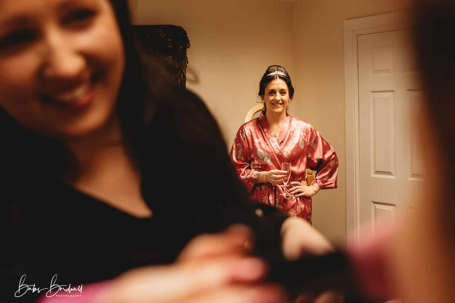 bride smiling looking at her bridesmaid having her make-up done
