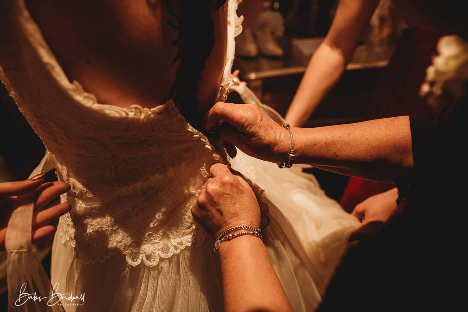 bride putting her dress on assisted by her mother and bridesmaid