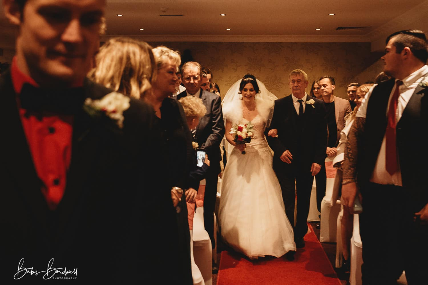 groom being walked down the aisle by her father at Holt Lodge North Wales with groom nervously looking on