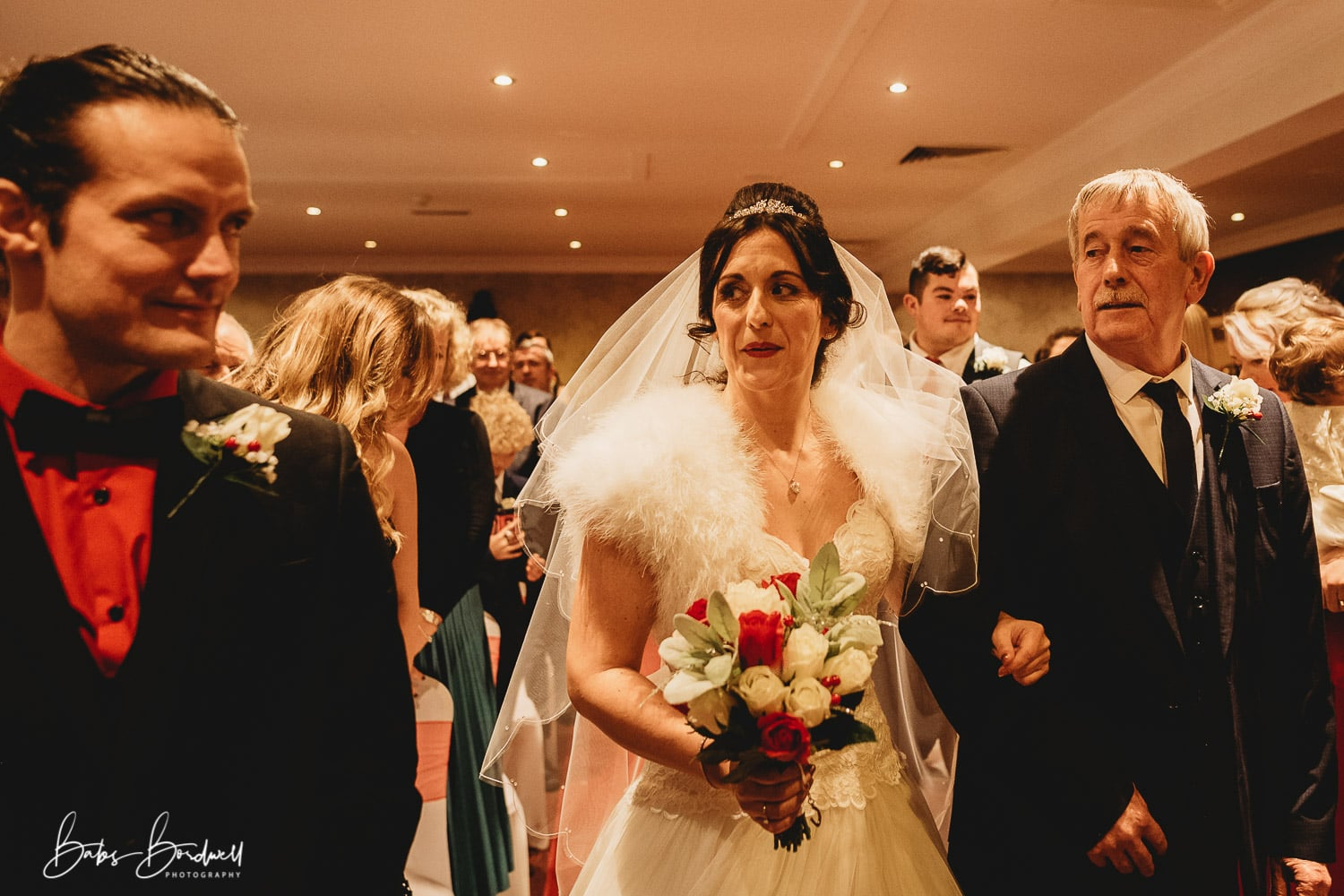 nervous bride being walked down the aisle by her father looking at her groom for the first time at Holt Lodge North Wales