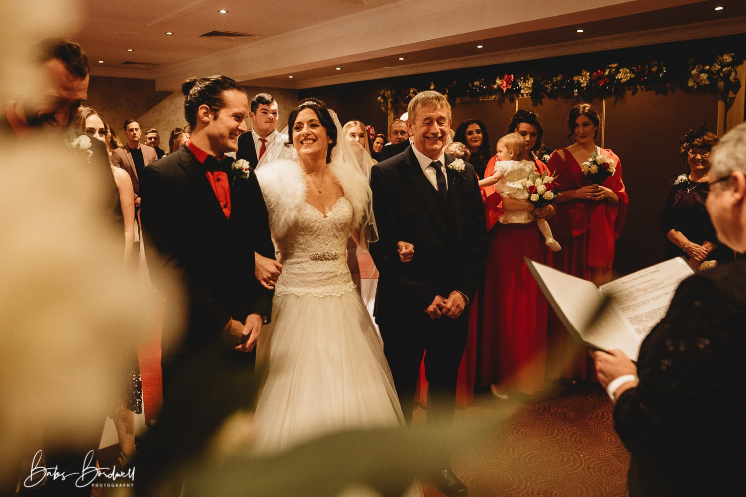 bride happily smiling at her groom while holding her father's arm