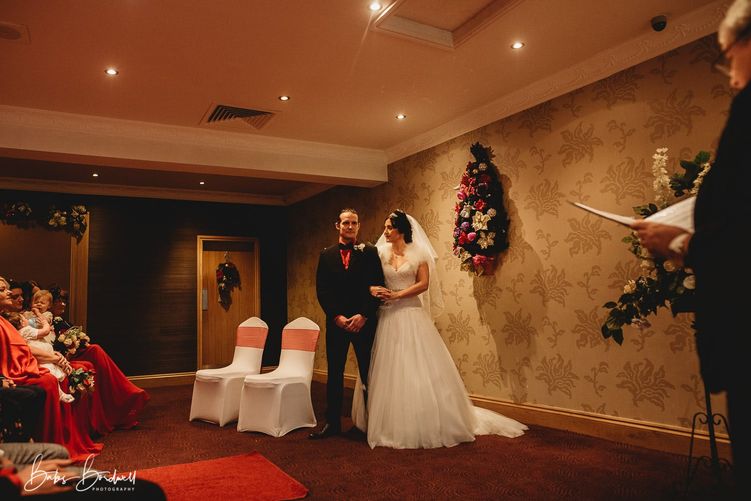 bride and groom linking arms in ceremony room of Holt Lodge North Wales