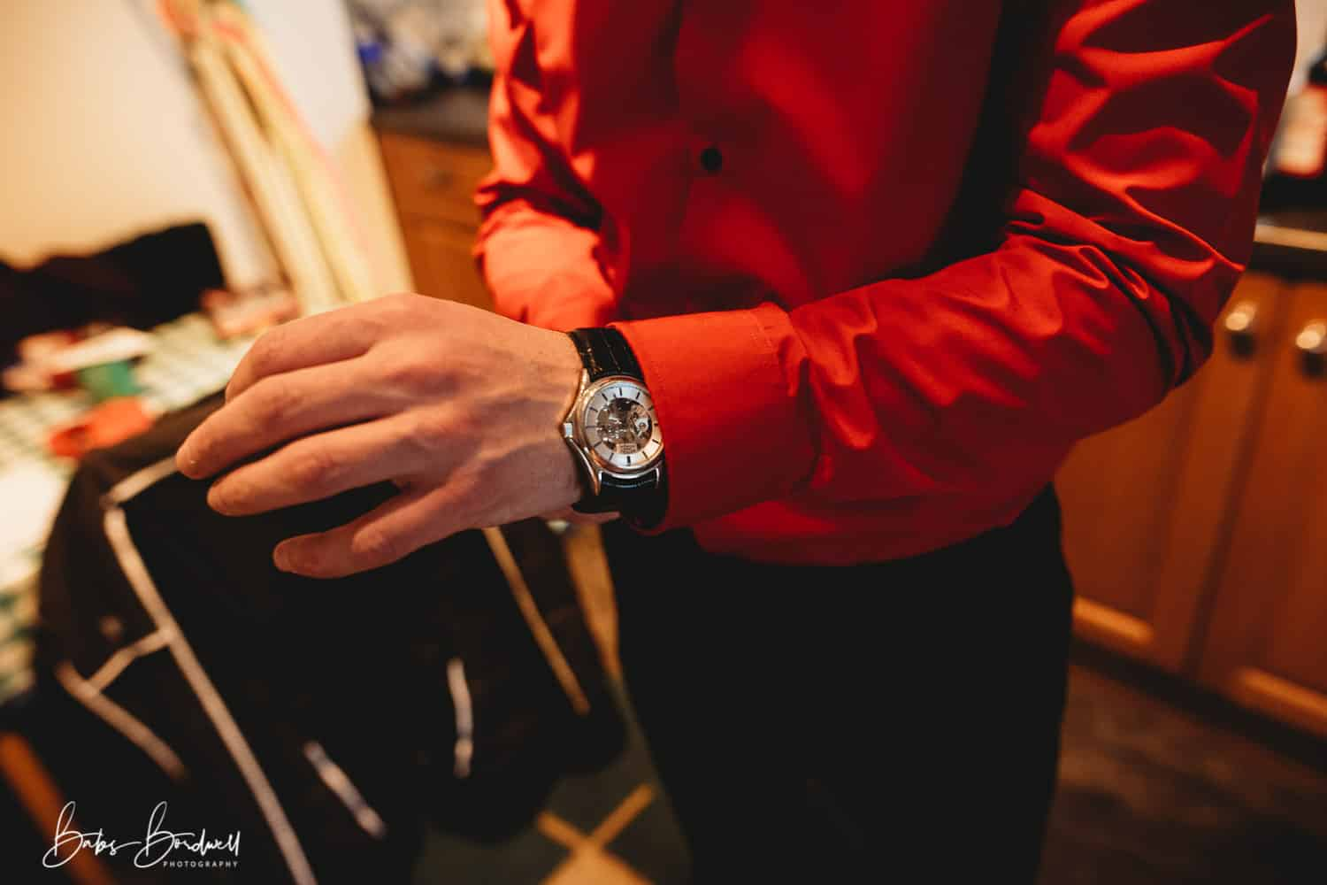 groom in red shirt adjusting his watch strap