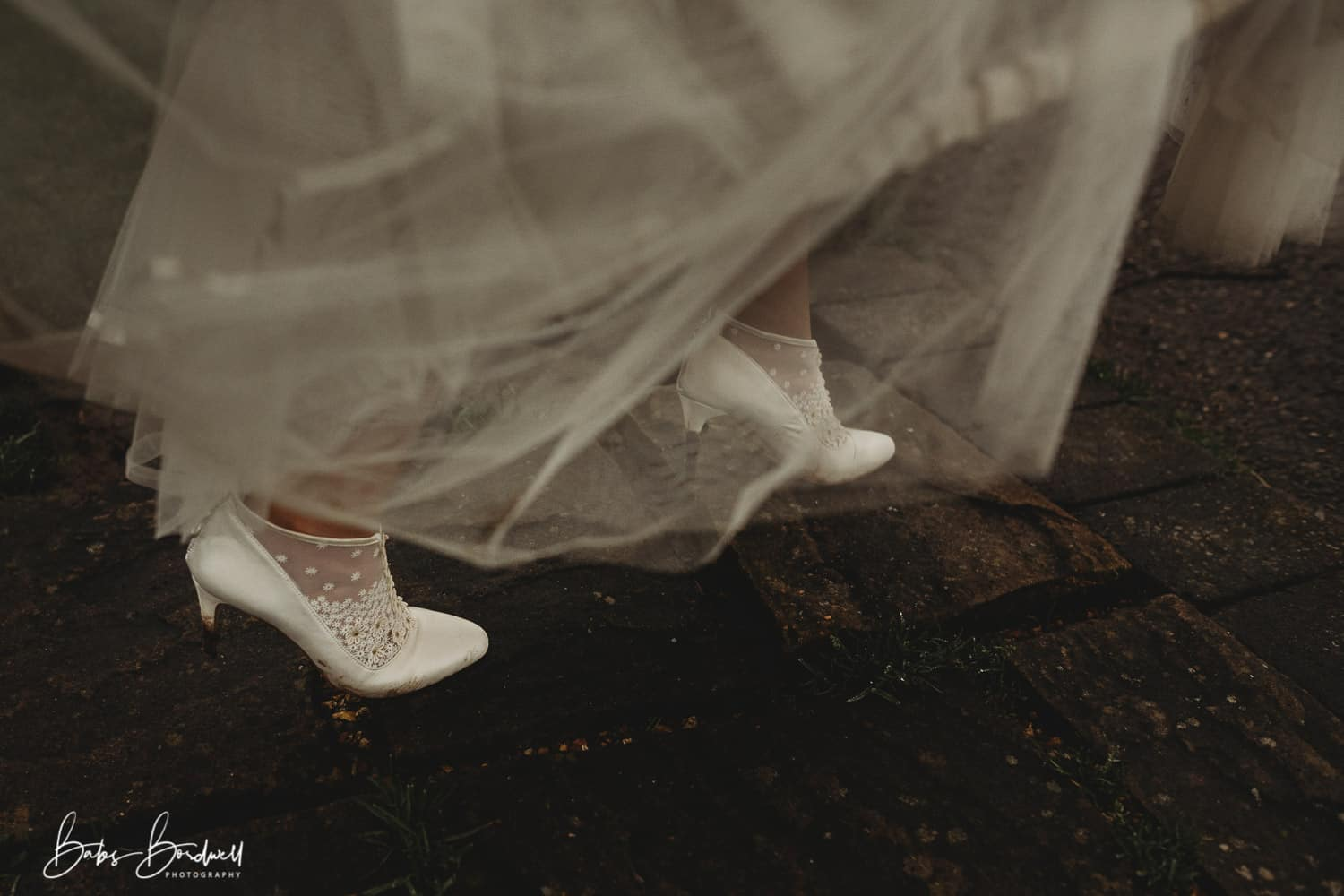 close-up of bride's mud caked shoes while holding up her dress North Wales Wedding Photographer at Holt Lodge