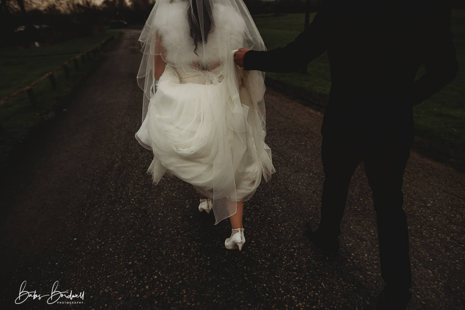 shot from behind of bride and groom walking with groom holding up bride's dress North Wales Wedding Photographer at Holt Lodge