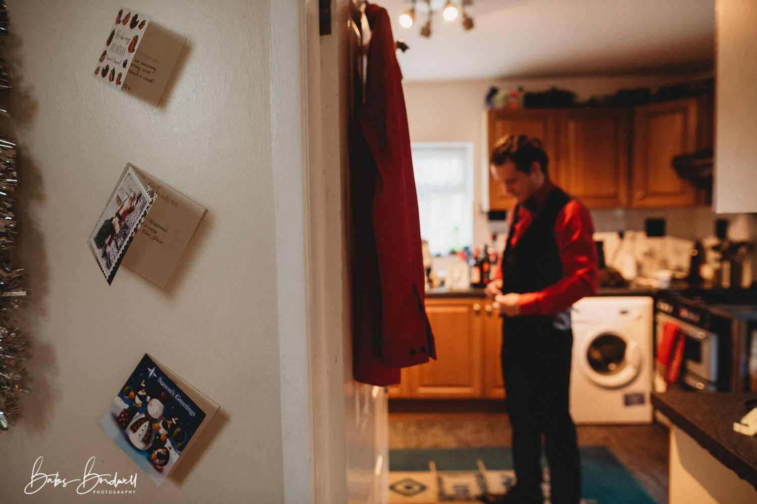 groom in red shirt doing his buttons up framed through kitchen door