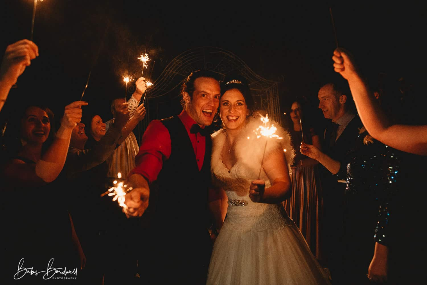 sparkler shot with bride and groom looking into camera smiling at Holt Lodge North Wales