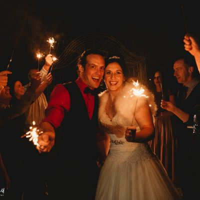Holt Lodge Wedding Photographer - couple having sparkler shots looking into the camera smiling