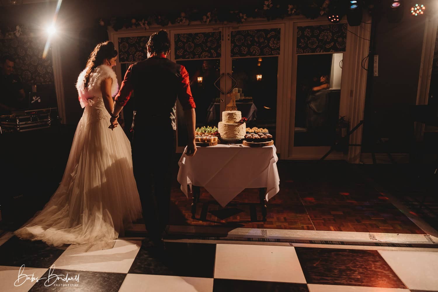 bride and groom holding hands walking up to table with their cake on the dance floor at Holt Lodge North Wales